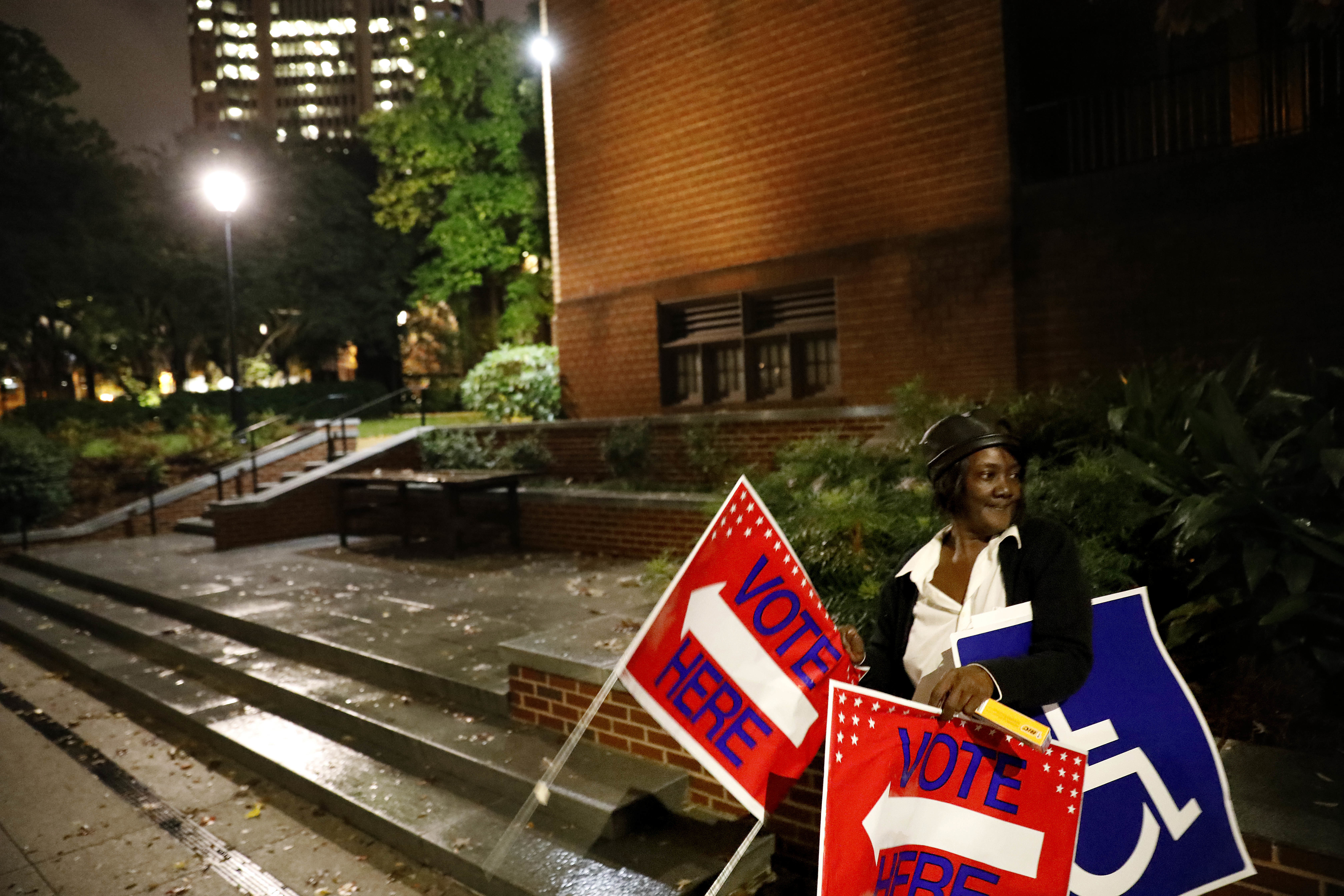 Poll worker Sarah Thomas places signs outside a precinct before polls open on election day in Atlanta, Nov. 6, 2018.