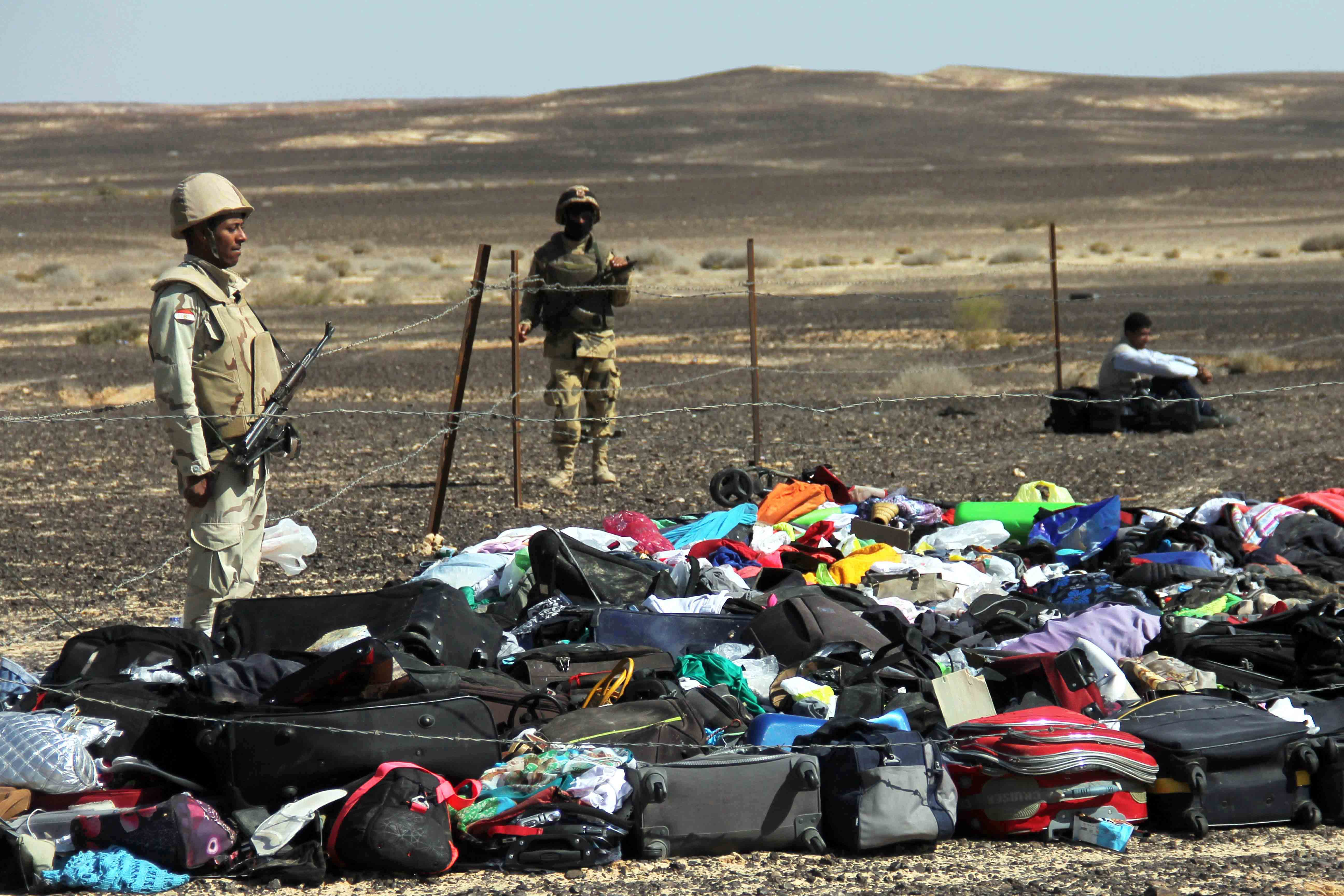 Egyptian Army soldiers stand near luggage and personal effects of passengers a day after a passenger jet bound for St. Petersburg, Russia crashed in Hassana, Egypt, Nov. 1, 2015.