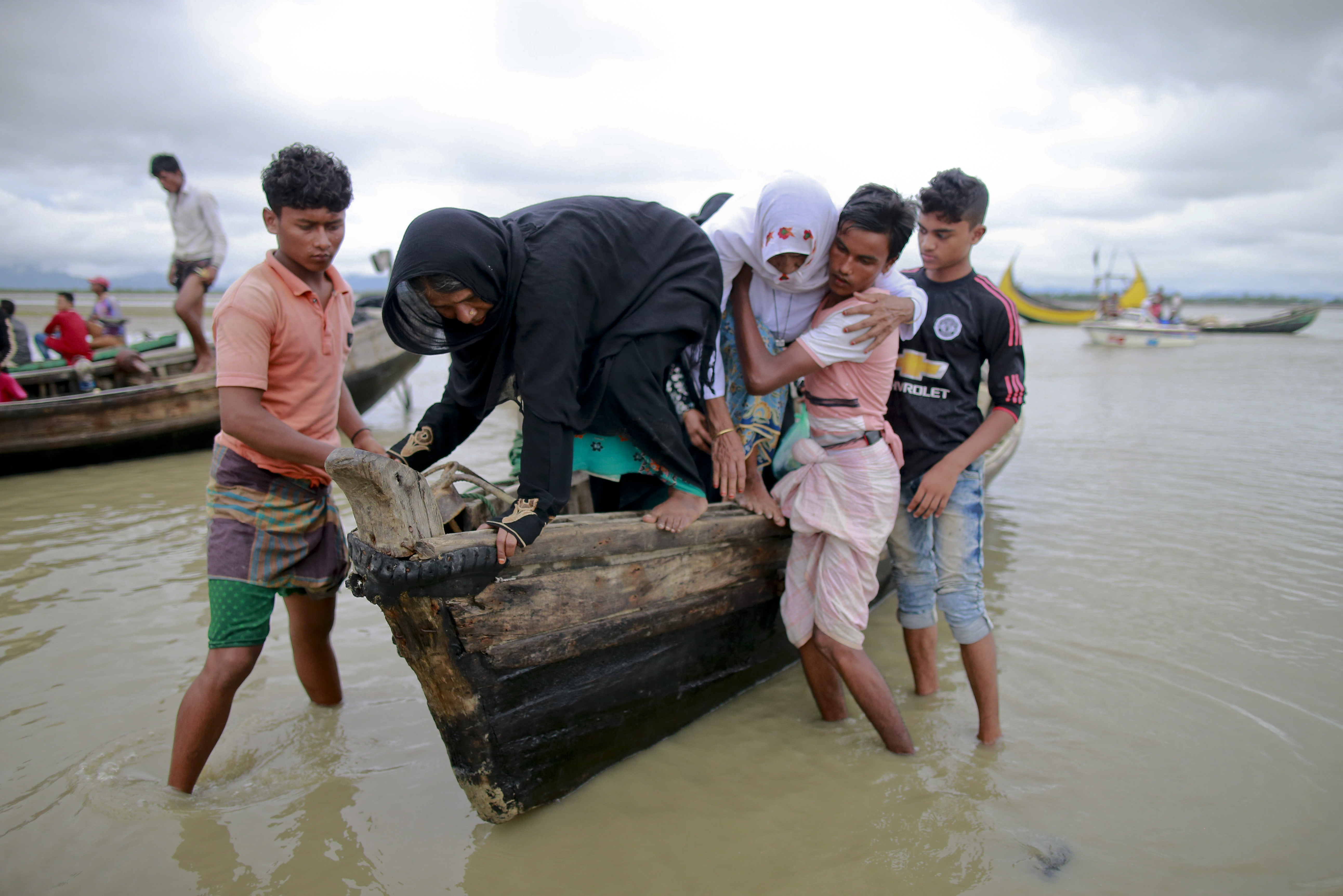 Bangladeshi villagers help two elderly Rohingya women from a boat after crossing a canal at Shah Porir Deep, in Teknak, Bangladesh, Aug. 31, 2017.