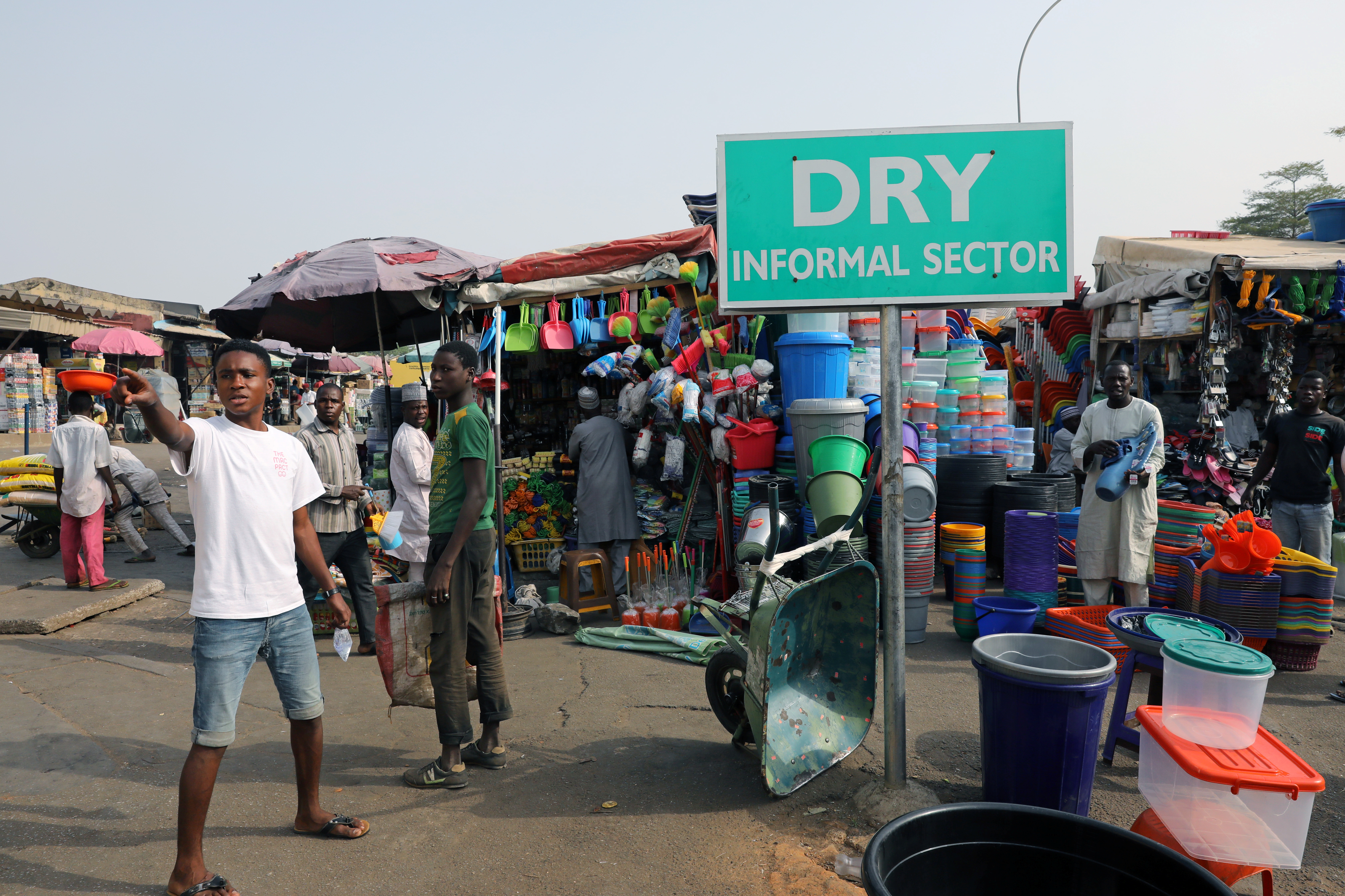 Men stand near displayed merchandise for sale around the informal sector at the Wuse market in Abuja, Nigeria, Jan. 30, 2018.