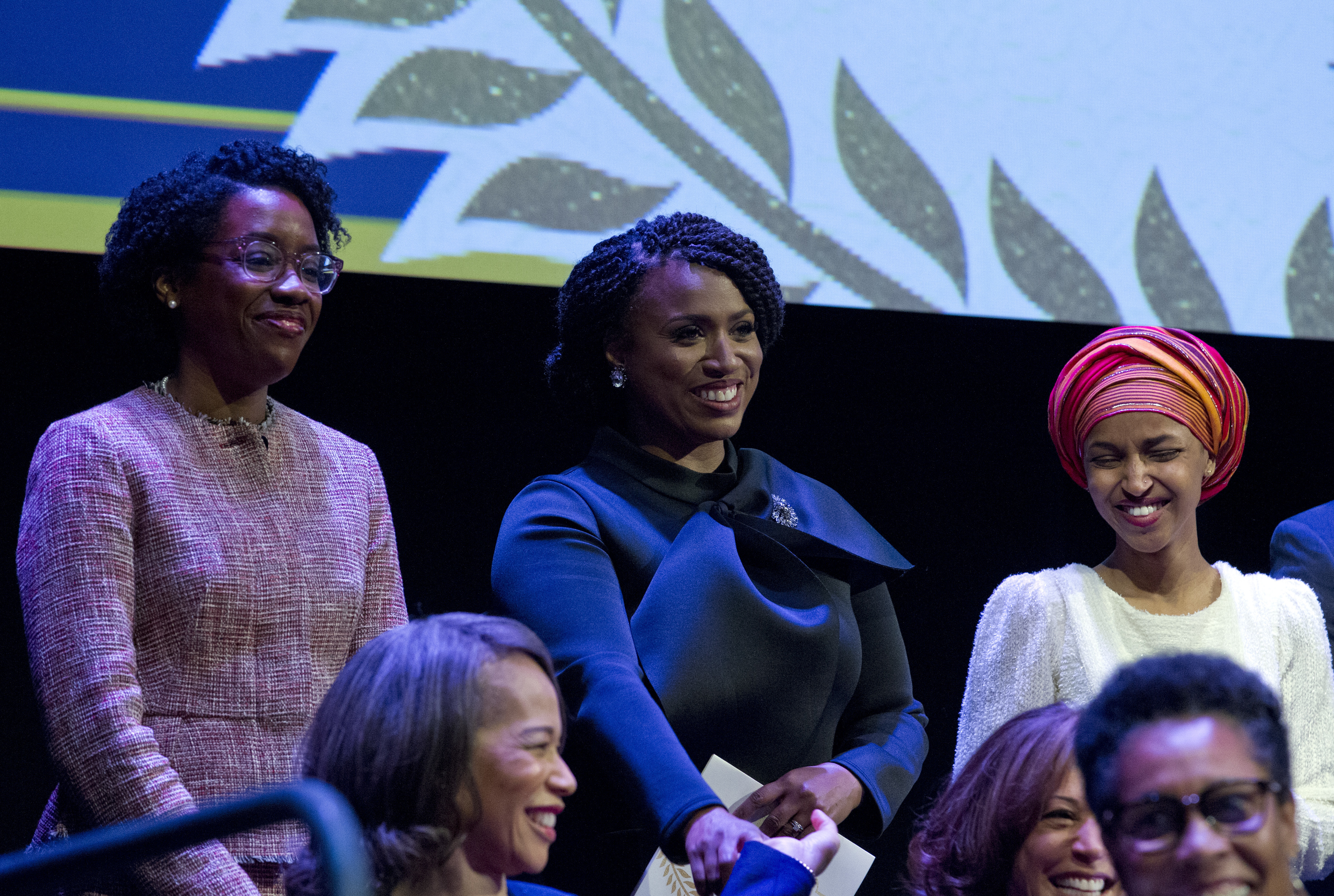 FILE - From left, Lauren Underwood, D-Ill., Ayanna Pressley, D-Mass., and Ilhan Omar D-Minn., are pictured during the swearing-in ceremony of Congressional Black Caucus members of the 116th Congress at the Warner Theatre in Washington, Jan. 3, 2019. ...