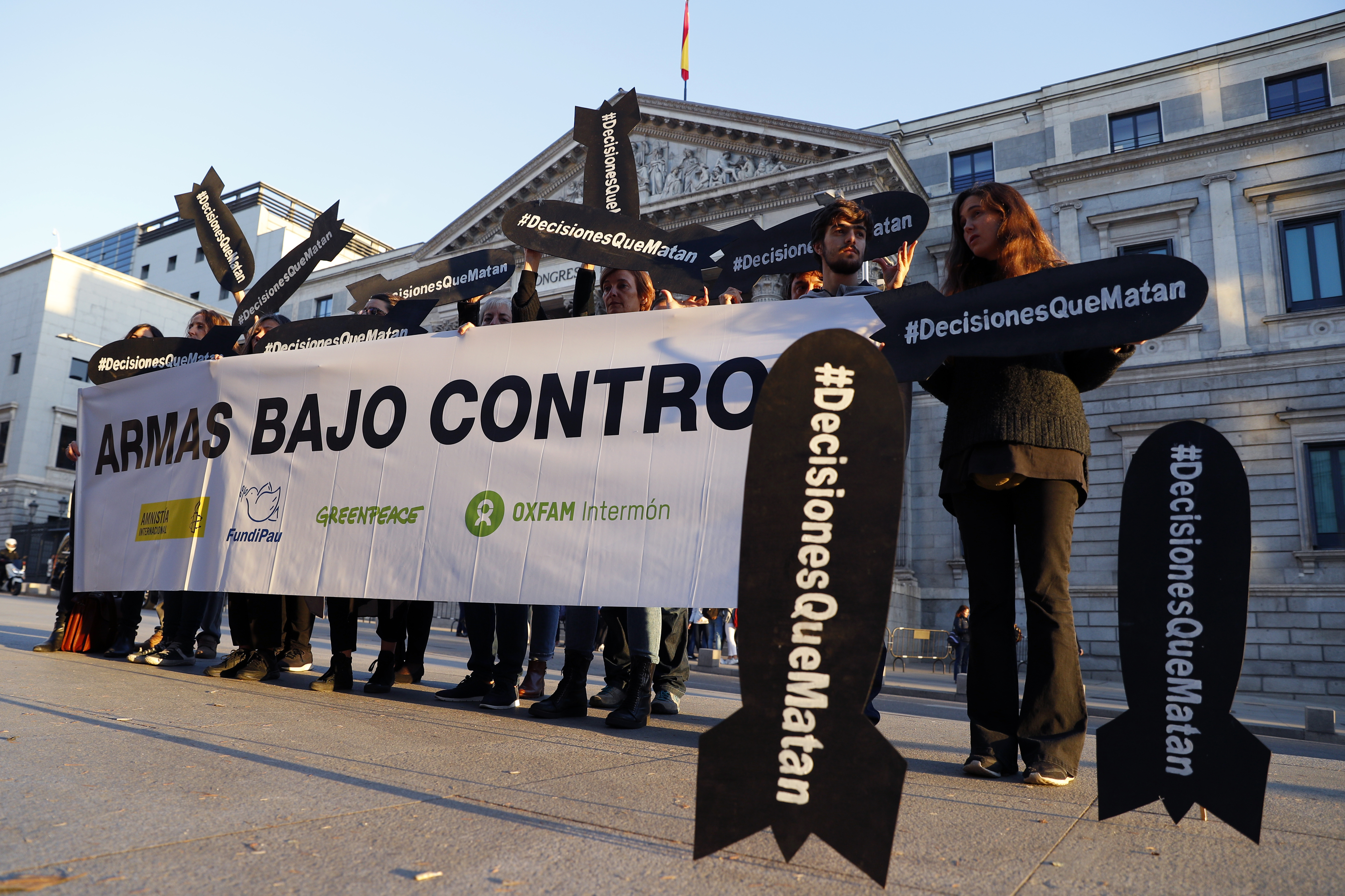"""People hold placards reading """"Decisions that kill"""" during a gathering to demand a halt of arm sales to Saudi Arabia outside Parliament in Madrid, Oct. 24, 2018."""