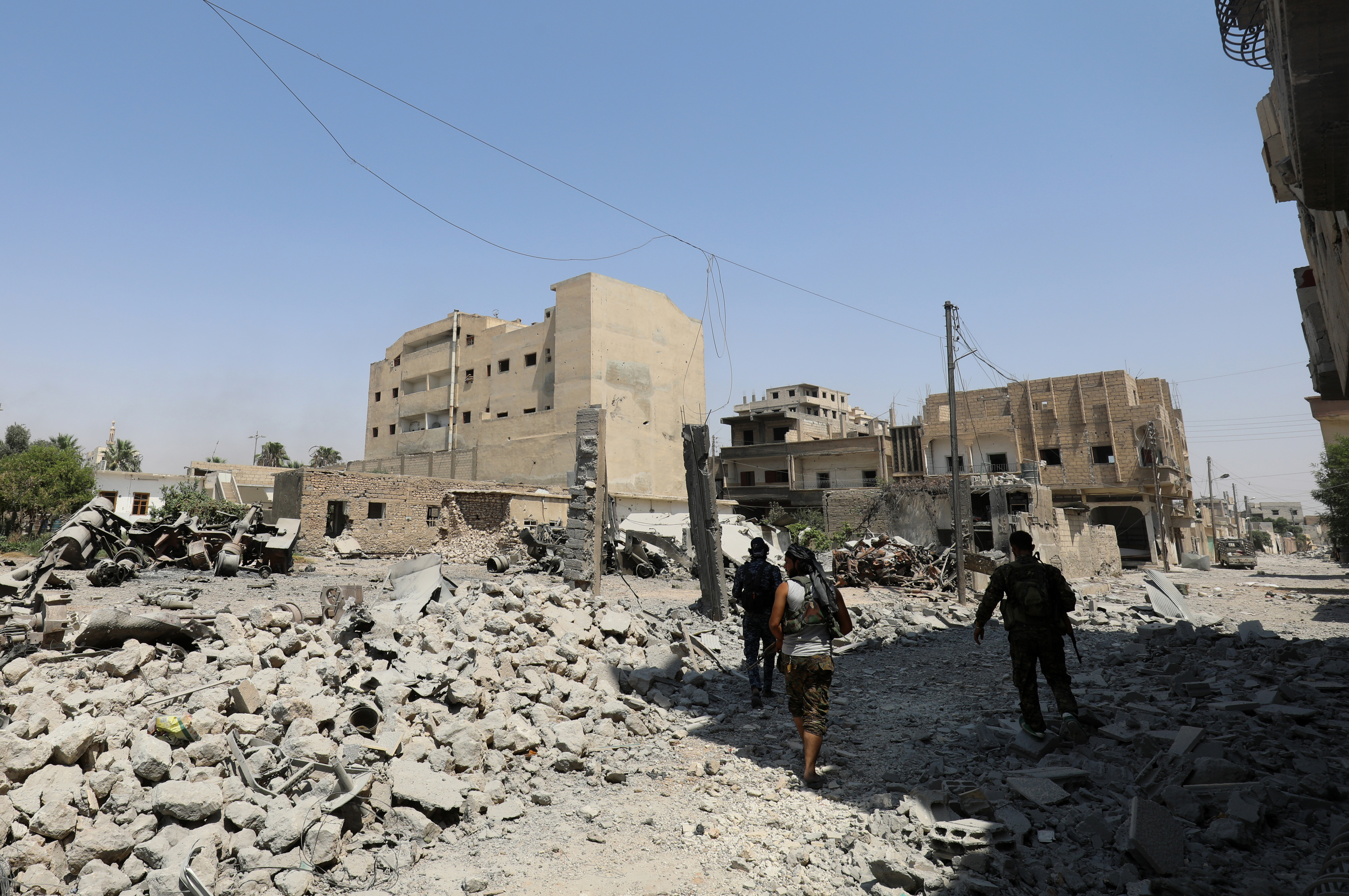FILE - Fighters from the Syrian Democratic Forces (SDF), a US-backed Kurdish-Arab alliance, walk through the rubble in an eastern area of the embattled city of Raqa in northern Syria on Aug. 15, 2017.