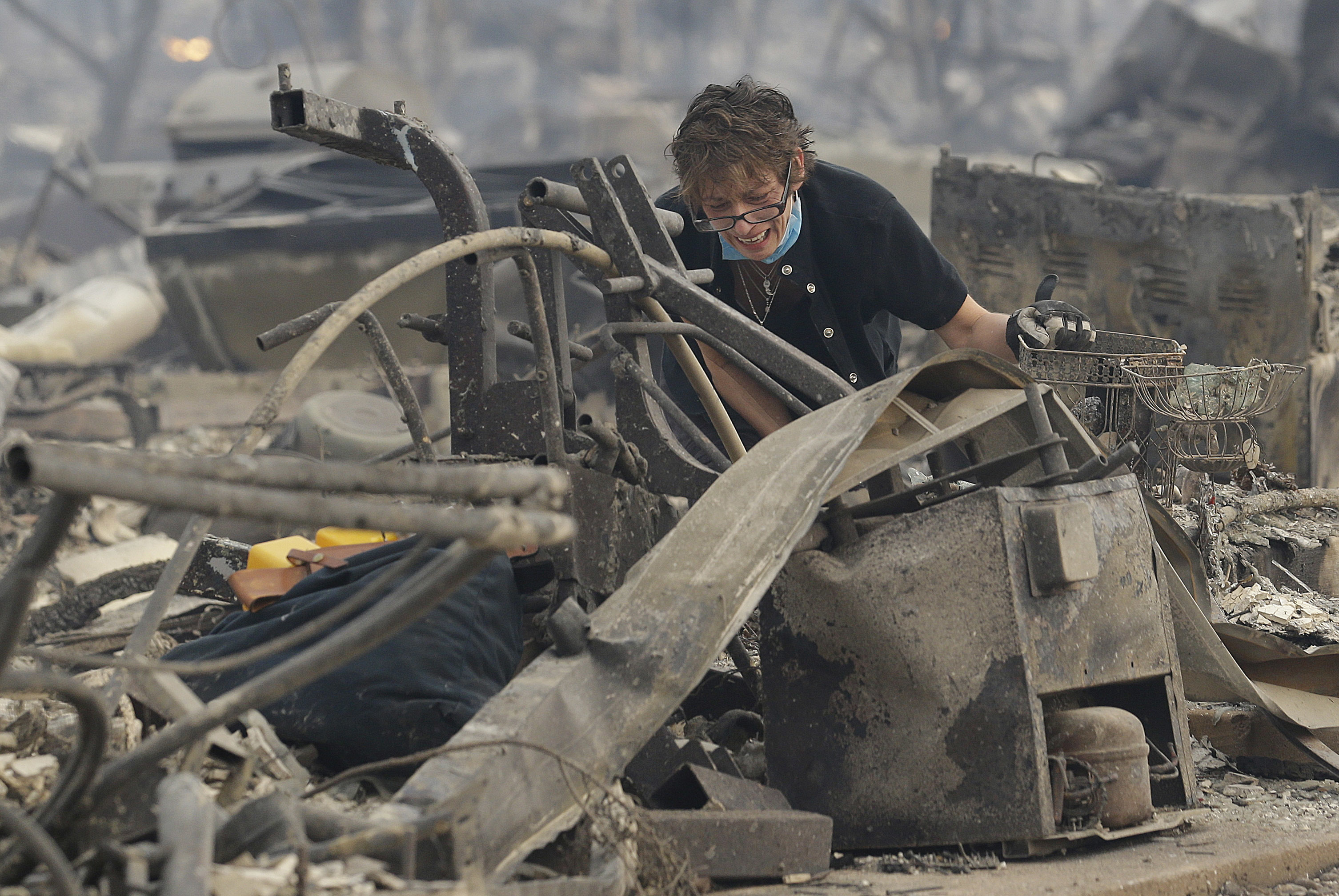 Kristine Pond searches the remains of her family's home destroyed by fires in Santa Rosa, Calif., Oct. 9, 2017.