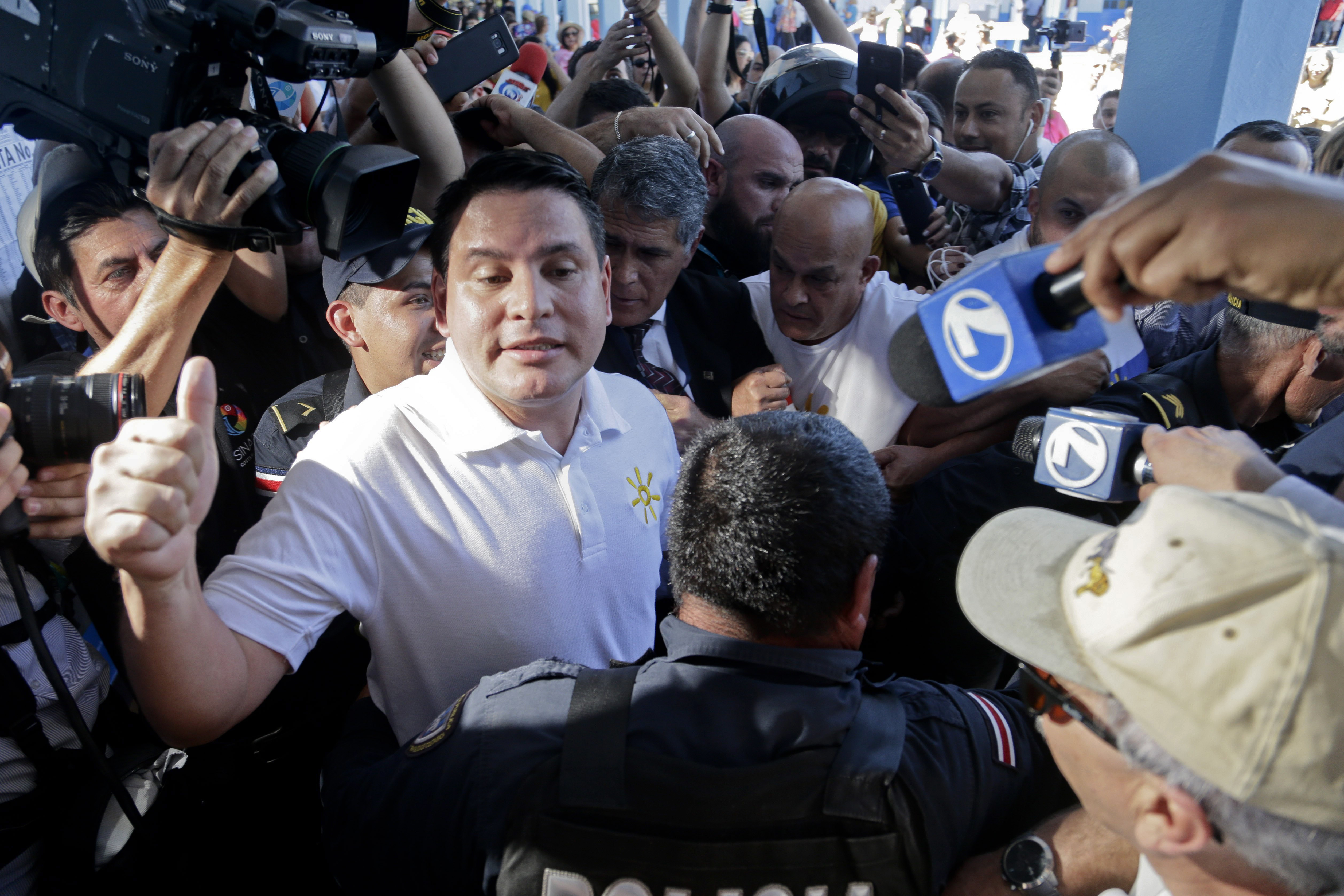Presidential candidate Fabricio Alvarado, with the National Restoration party, gives a thumbs-up as he's surrounded by the press at a polling station during general elections in San Jose, Costa Rica, Feb. 4, 2018.