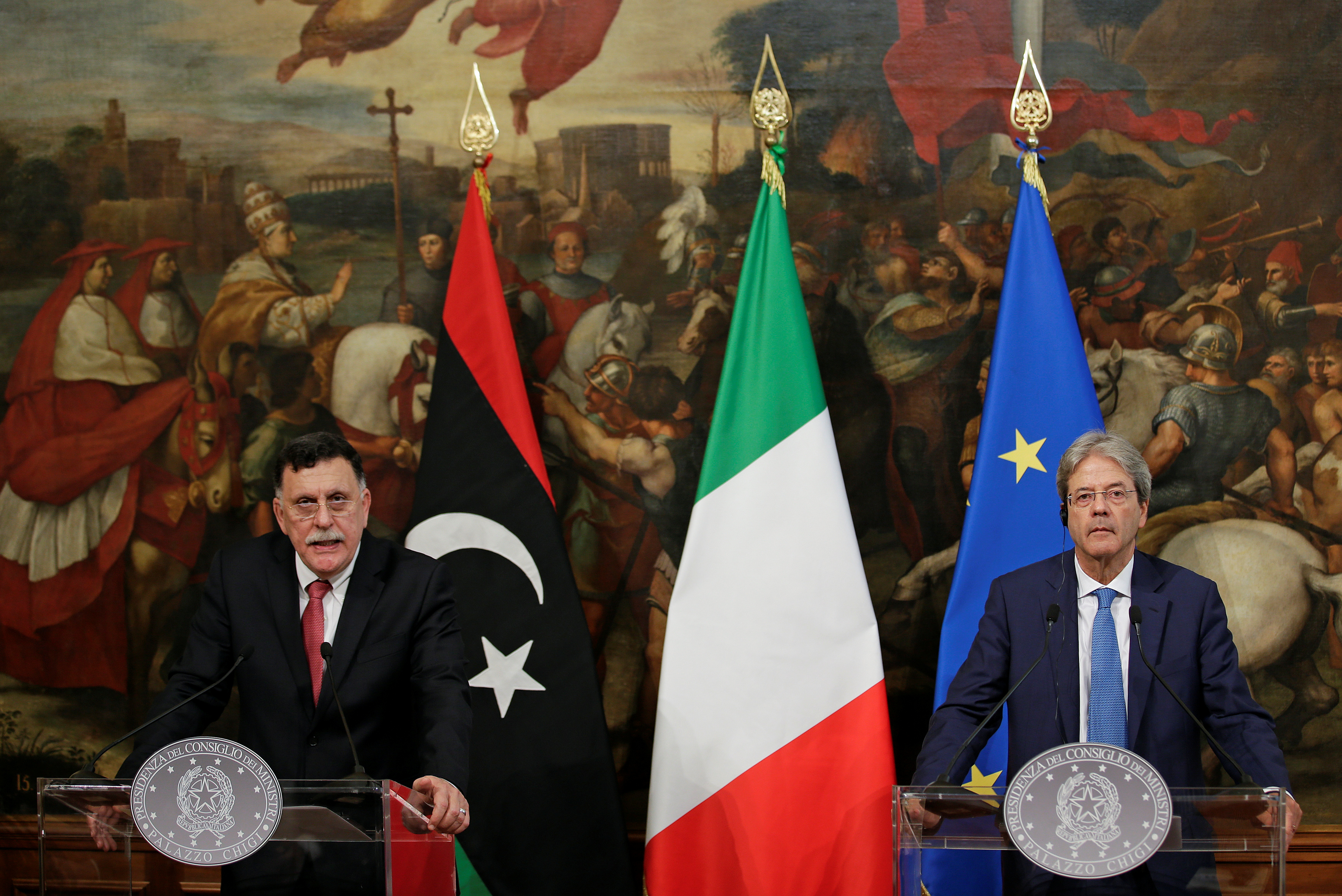 Italian Prime Minister Paolo Gentiloni (R) listens to his Libyan counterpart Fayez al-Sarraj during a news conference at Chigi Palace in Rome, Italy, July 26, 2017.