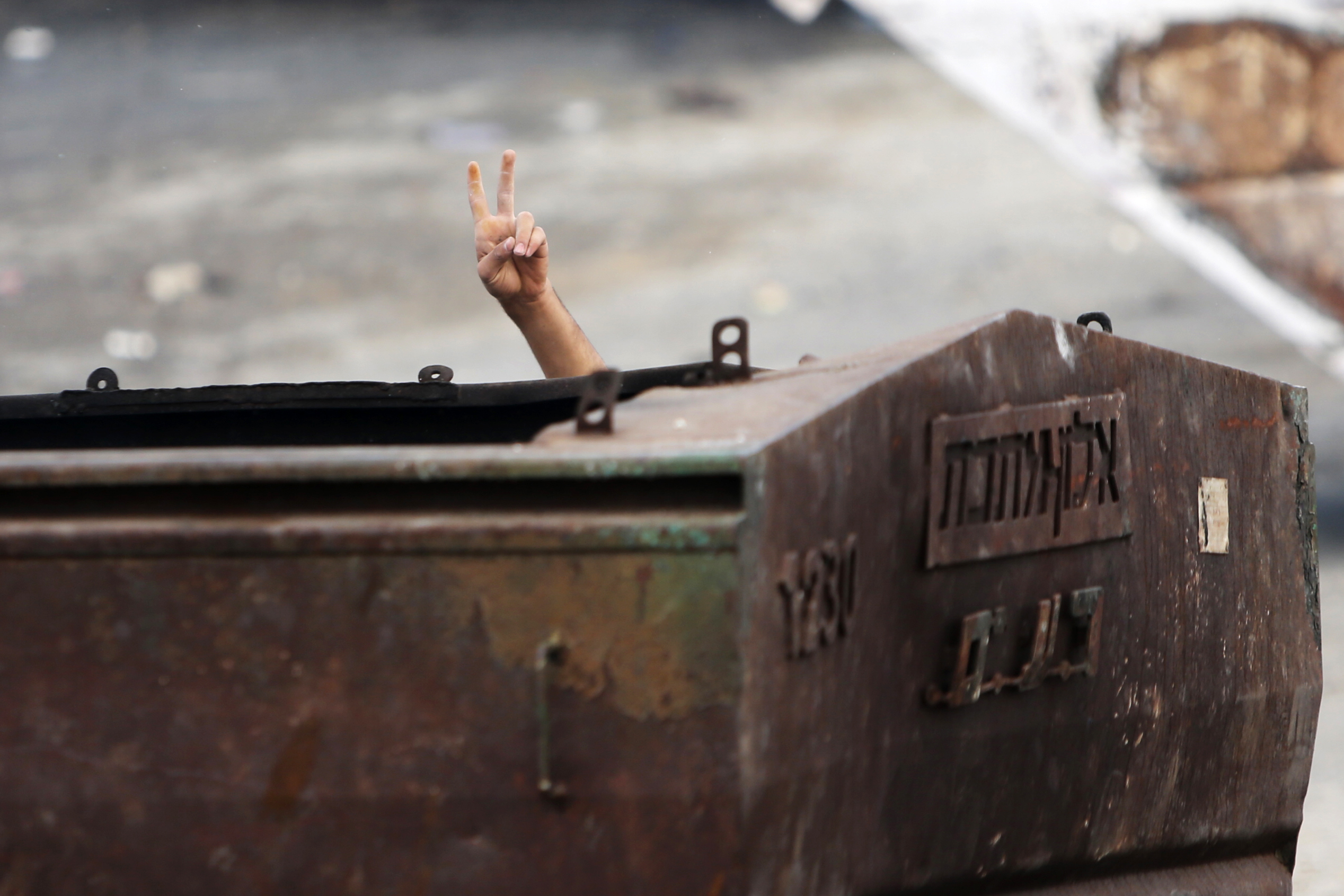 A Palestinian protester gestures as he hides behind a metal container during clashes with Israeli security forces in east Jerusalem October 30, 2014.  Israeli police on Thursday shot dead a 32-year-old Palestinian man suspected of having tried hours ...