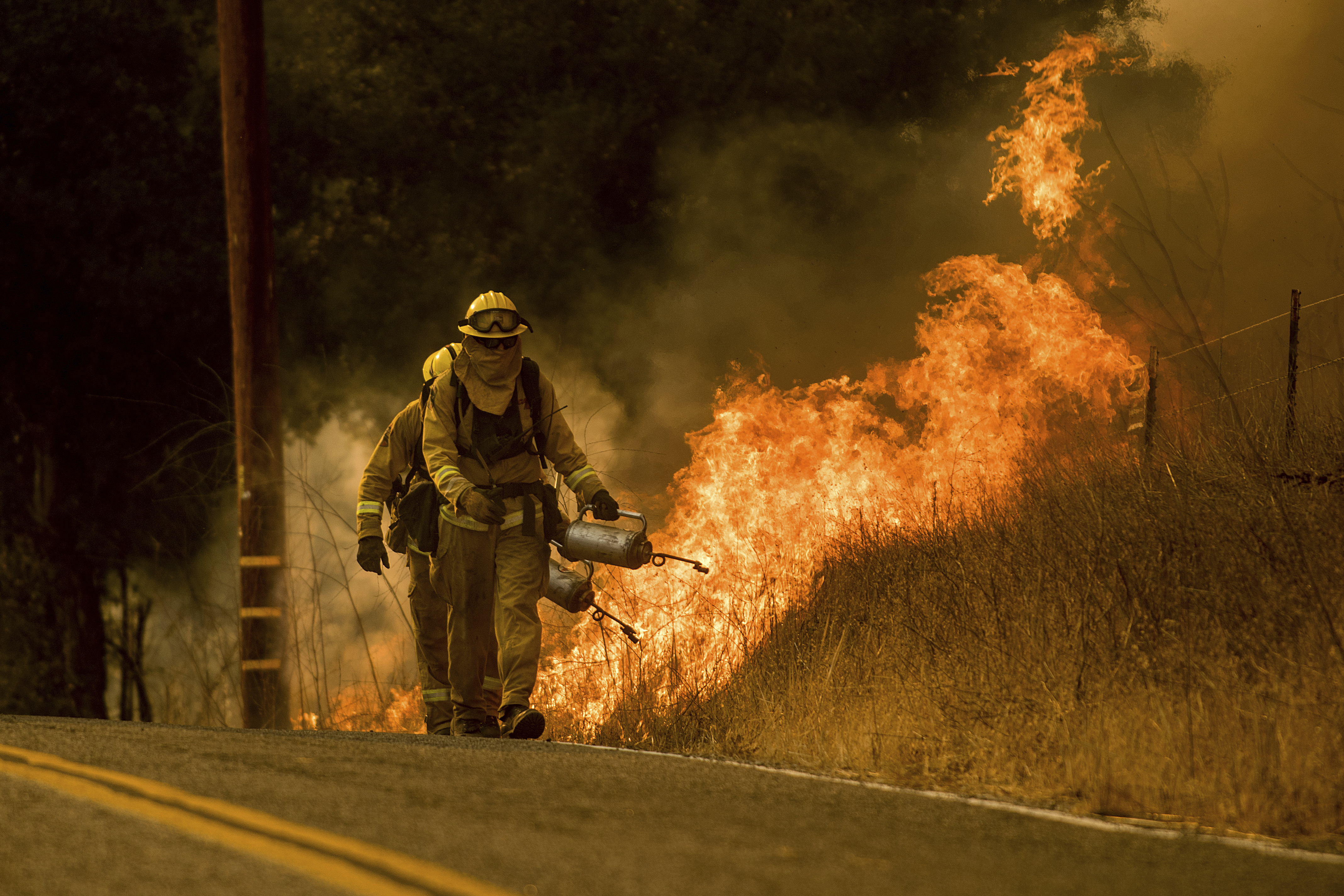 Firefighters light a backfire while trying to keep a wildfire from jumping Santa Ana Road near Ventura, Calif., Dec. 9, 2017.