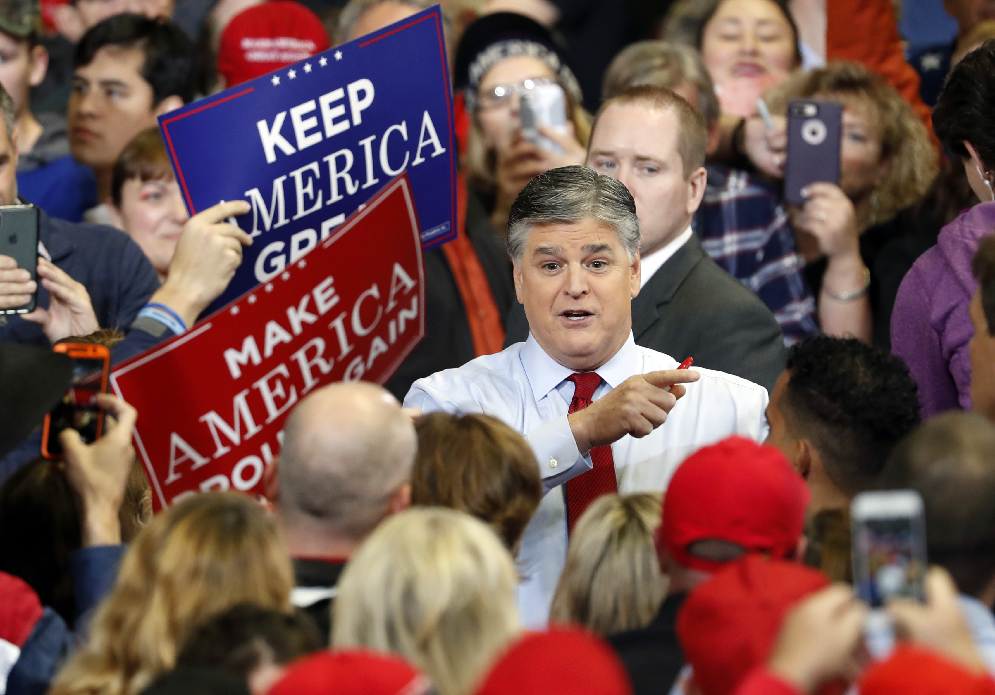 Television personality Sean Hannity speaks to members of the audience while signing autographs before the start of a campaign rally with President Donald Trump in Cape Girardeau, Mo., Nov. 5, 2018.
