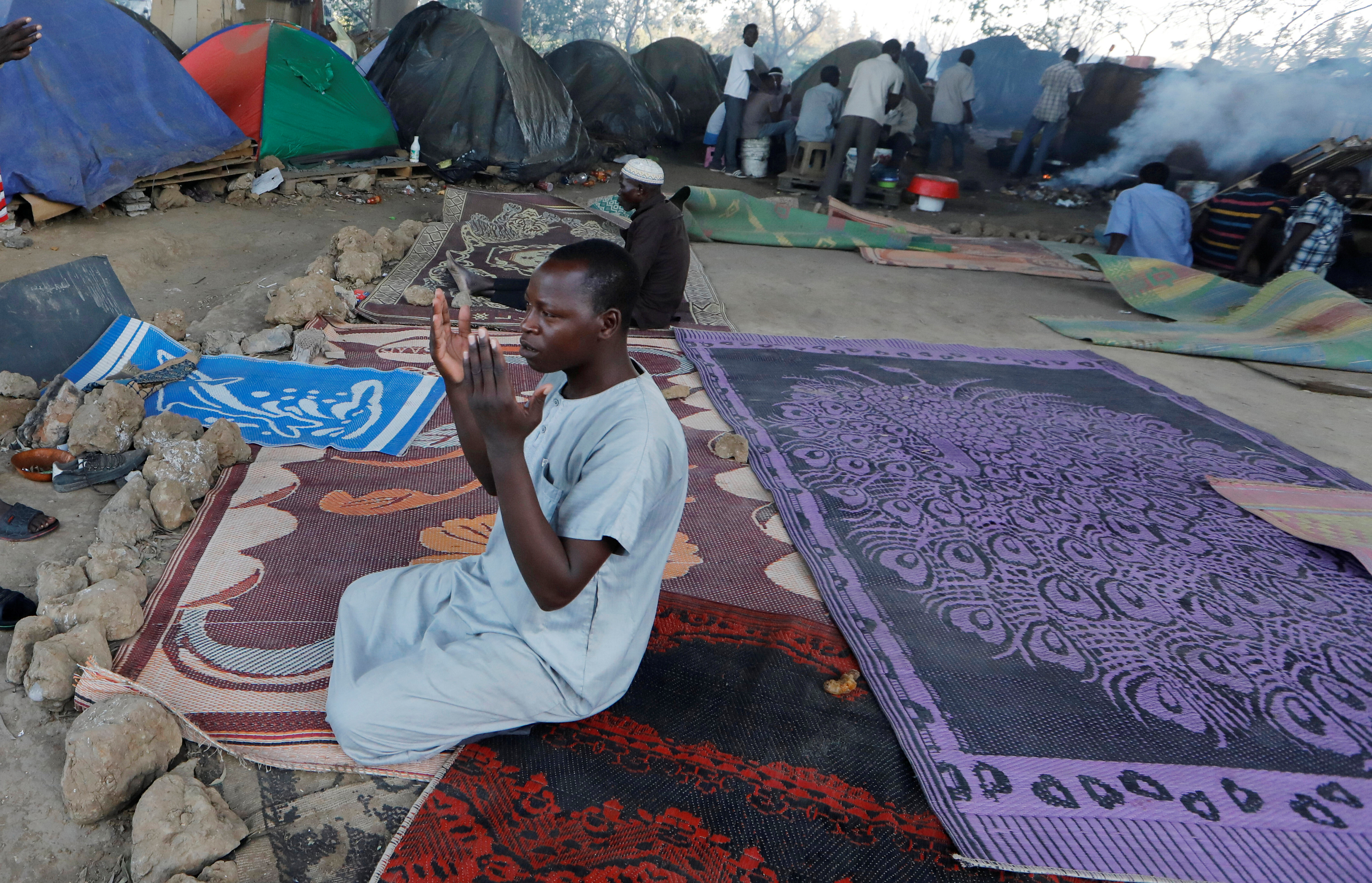 FILE - An African migrant prays near tents at a makeshift camp set up under the bridge of a motorway on the outskirts of Algiers, Algeria, June 28, 2017.