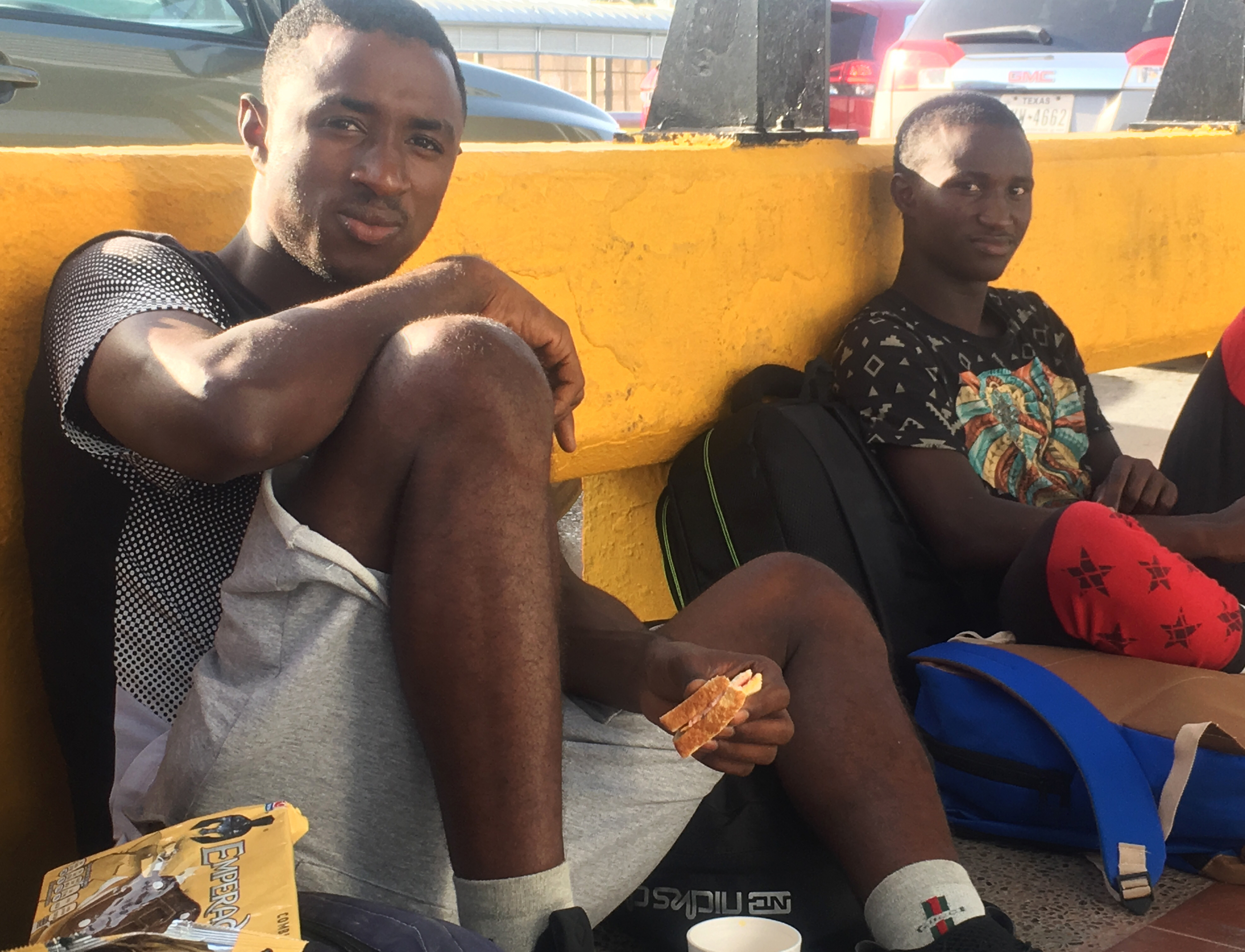 Mamadou Aliou Barry, left, departed from his native Guinea in West Africa when he was 14, a few years ago, waits for entry to the U.S. on the Gateway Bridge in Matamoros, Mexico, which connects to Brownsville, Texas, July 3, 2018. He said as part of ...