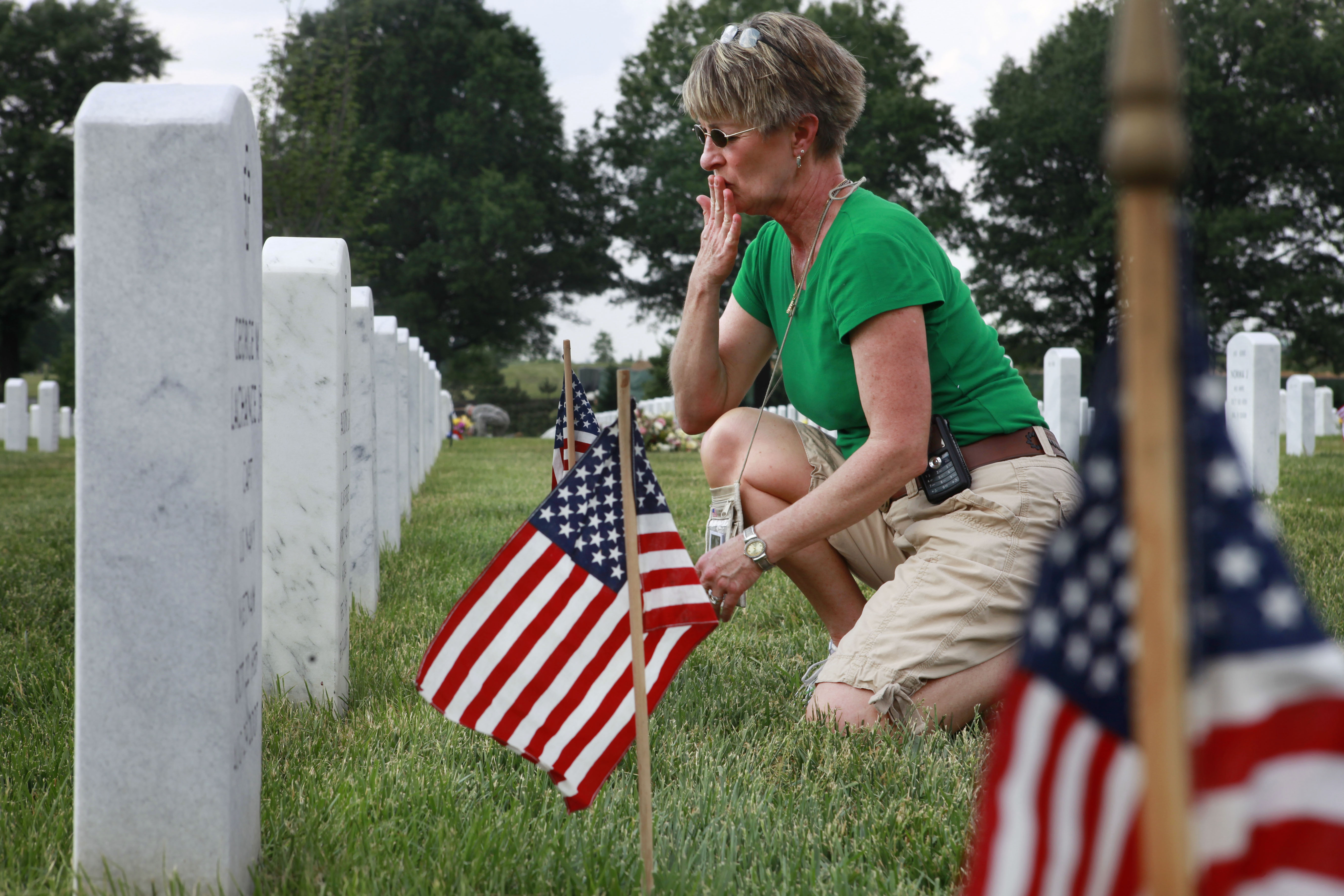 Anita Dixon, of Wichita, Kan., whose son Army Sgt. Evan Parker was killed while serving in Iraq in 2005, kisses the graves in section 60, where many of the casualties from Iraq and Afghanistan are buried, among flags placed in preparation of Memorial...
