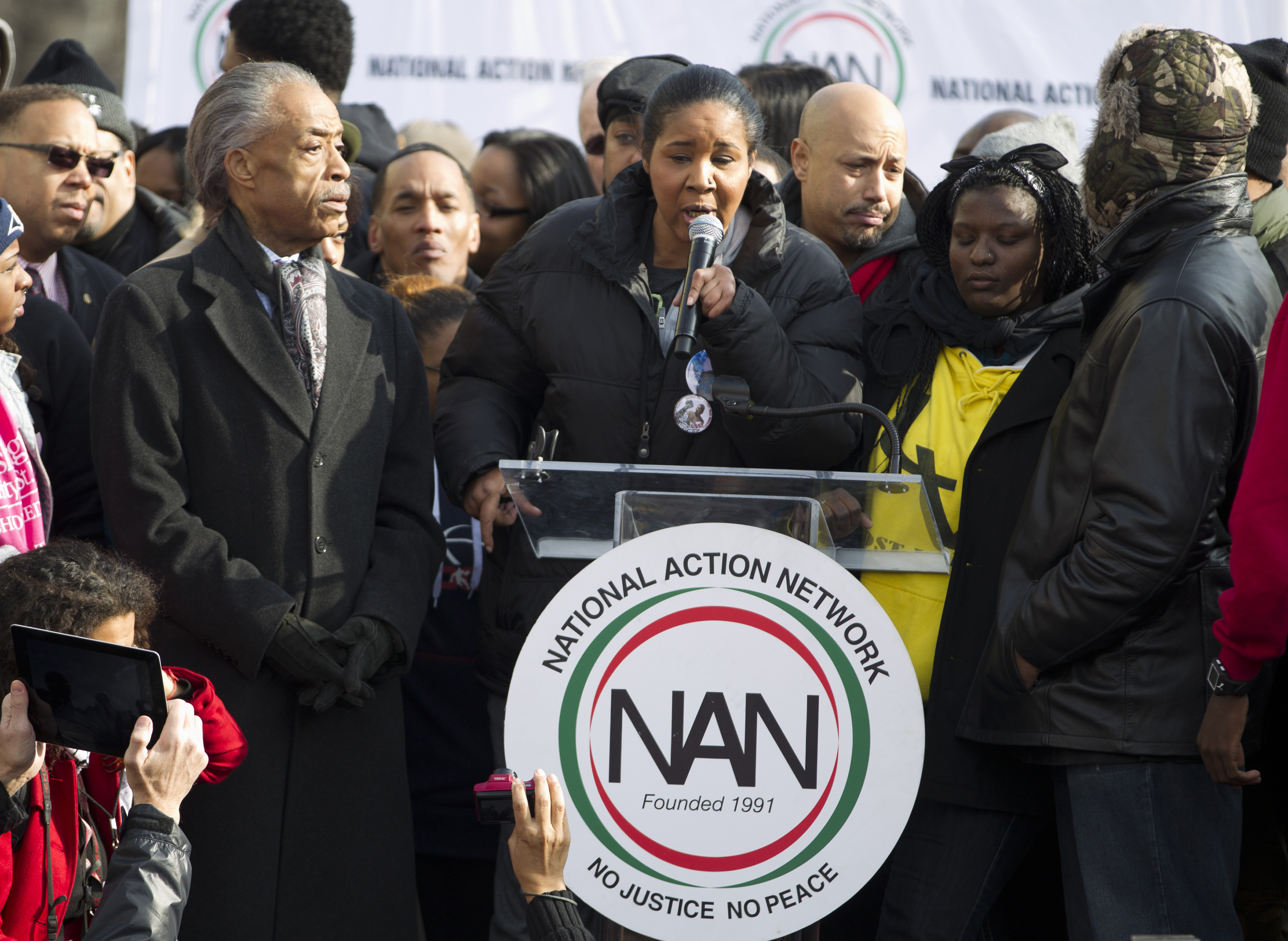 The Reverend Al Sharpton, left, listens as Eric Garner's widow Esaw speaks during a demonstration at Freedom Plaza in Washington, Dec. 13, 2014.