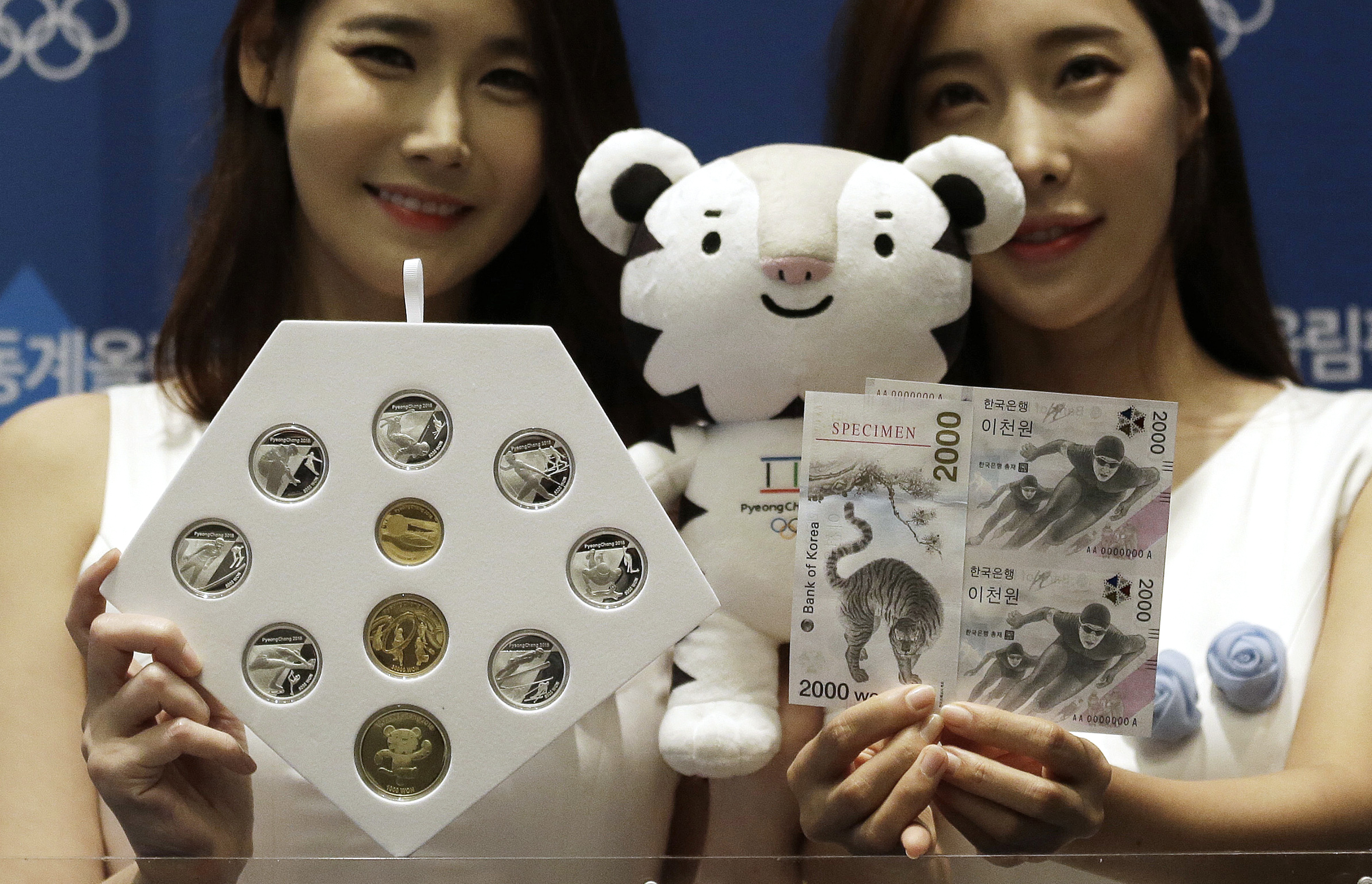 Models pose with the commemorative coins and bank notes for the 2018 Winter Olympic Games during the launching ceremony in Seoul, South Korea, Sept. 1, 2017.
