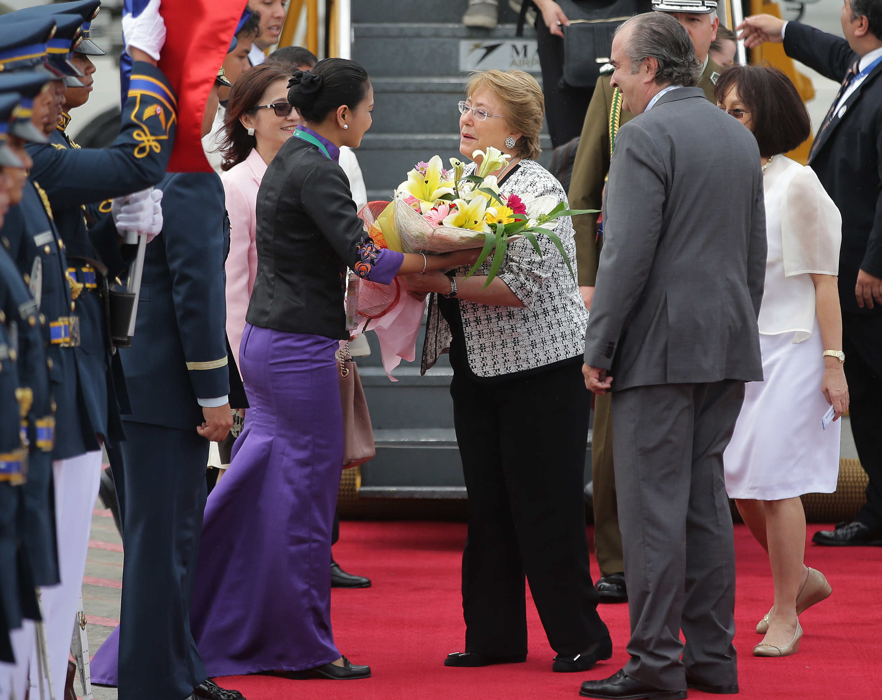 Chile's President Michelle Bachelet, center right, receives flowers as she arrives at Manila's international airport, Philippines, Nov. 15, 2015.