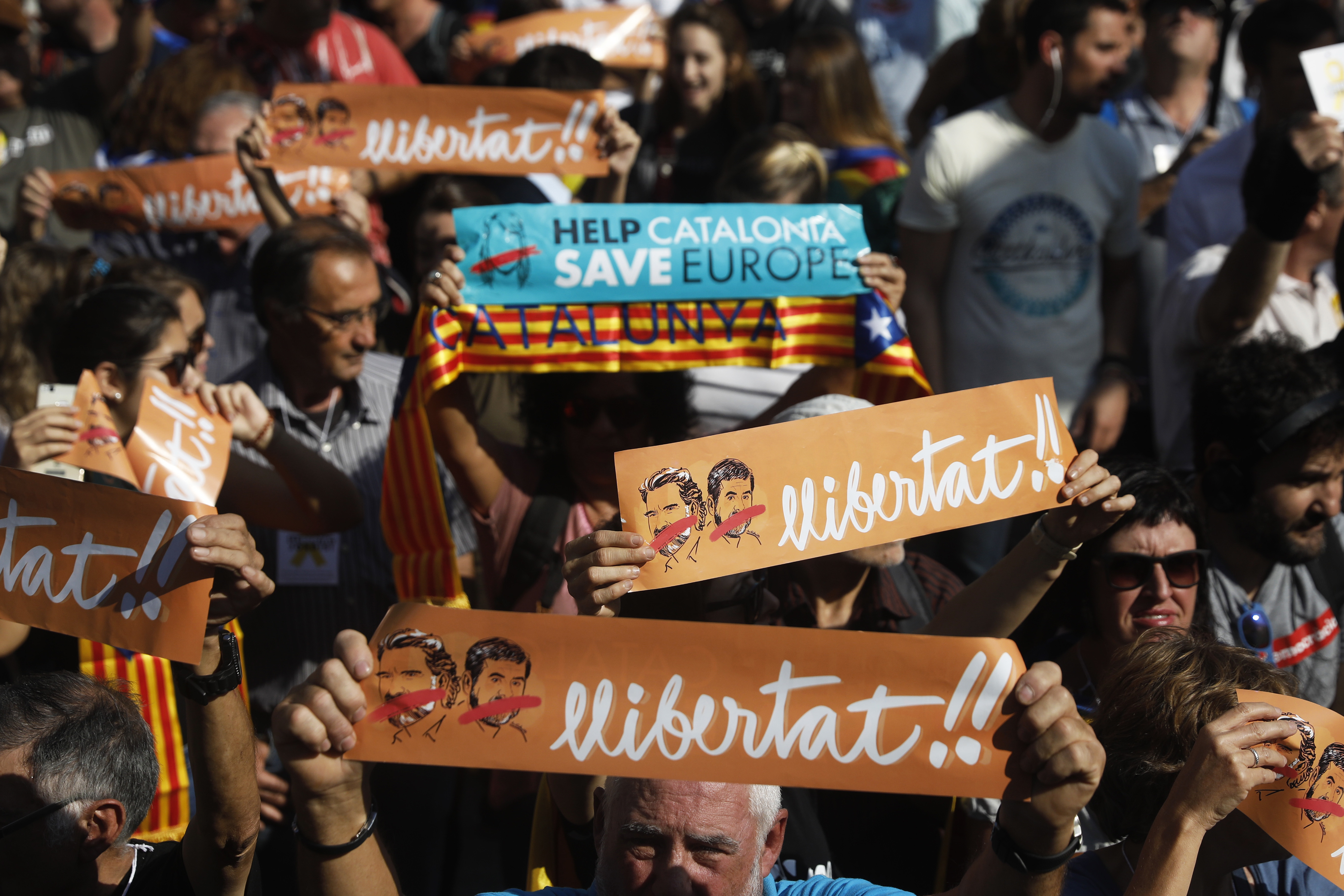 FILE - Protesters holds banners that read in Catalan '' freedom'' showing the portraits of the inprisoned Jordi Sanchez and Jordi Cuixart, leaders of the Catalan grassroots organizations Catalan National Assembly and Omnium Cultural, during a rally o...