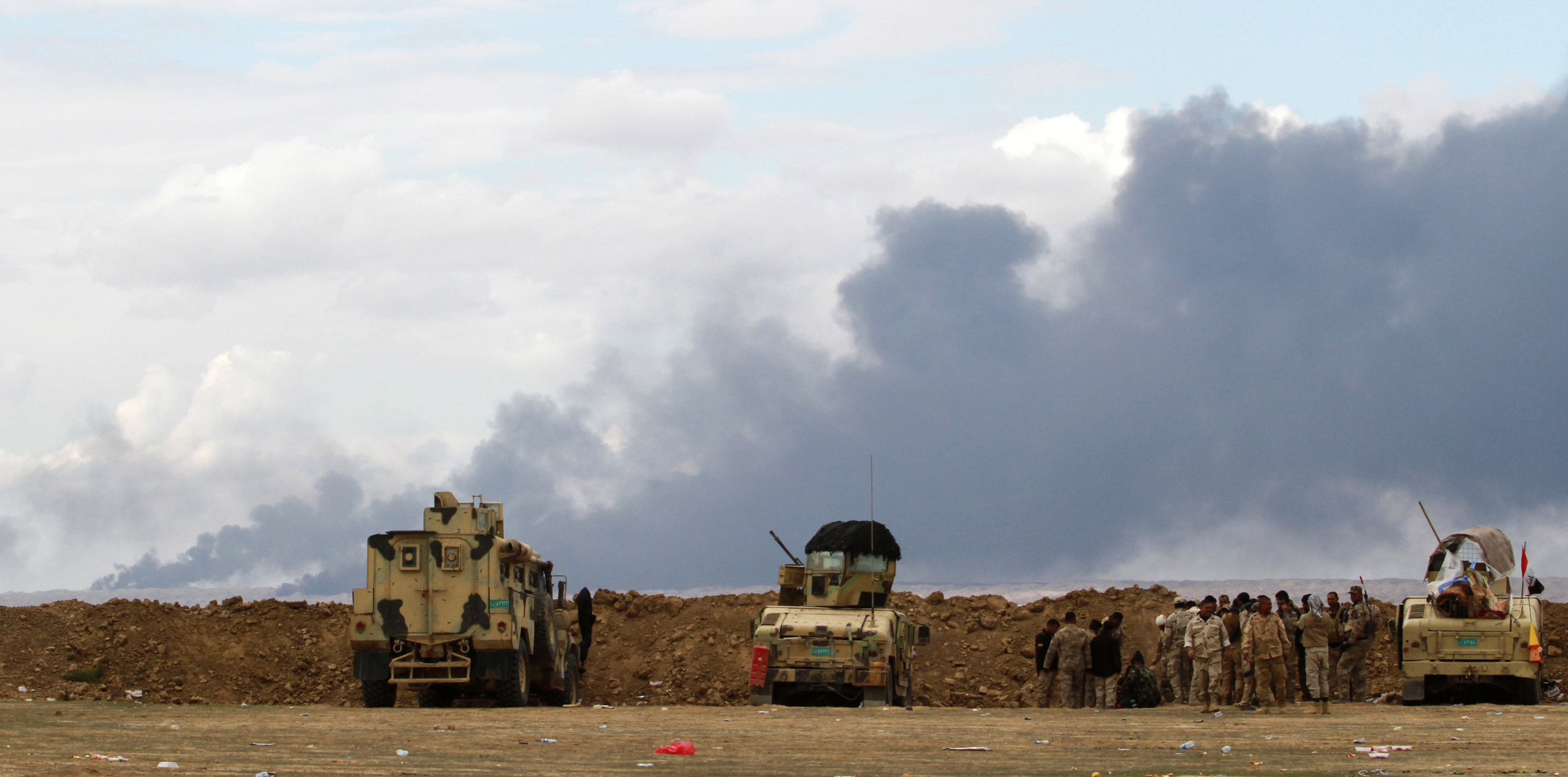 Iraqi soldiers gather near vehicles as smoke rises from oil wells in the Ajil field east of Tikrit in the Salahuddin province that were set on fire by Islamic State militants, March 4, 2015.