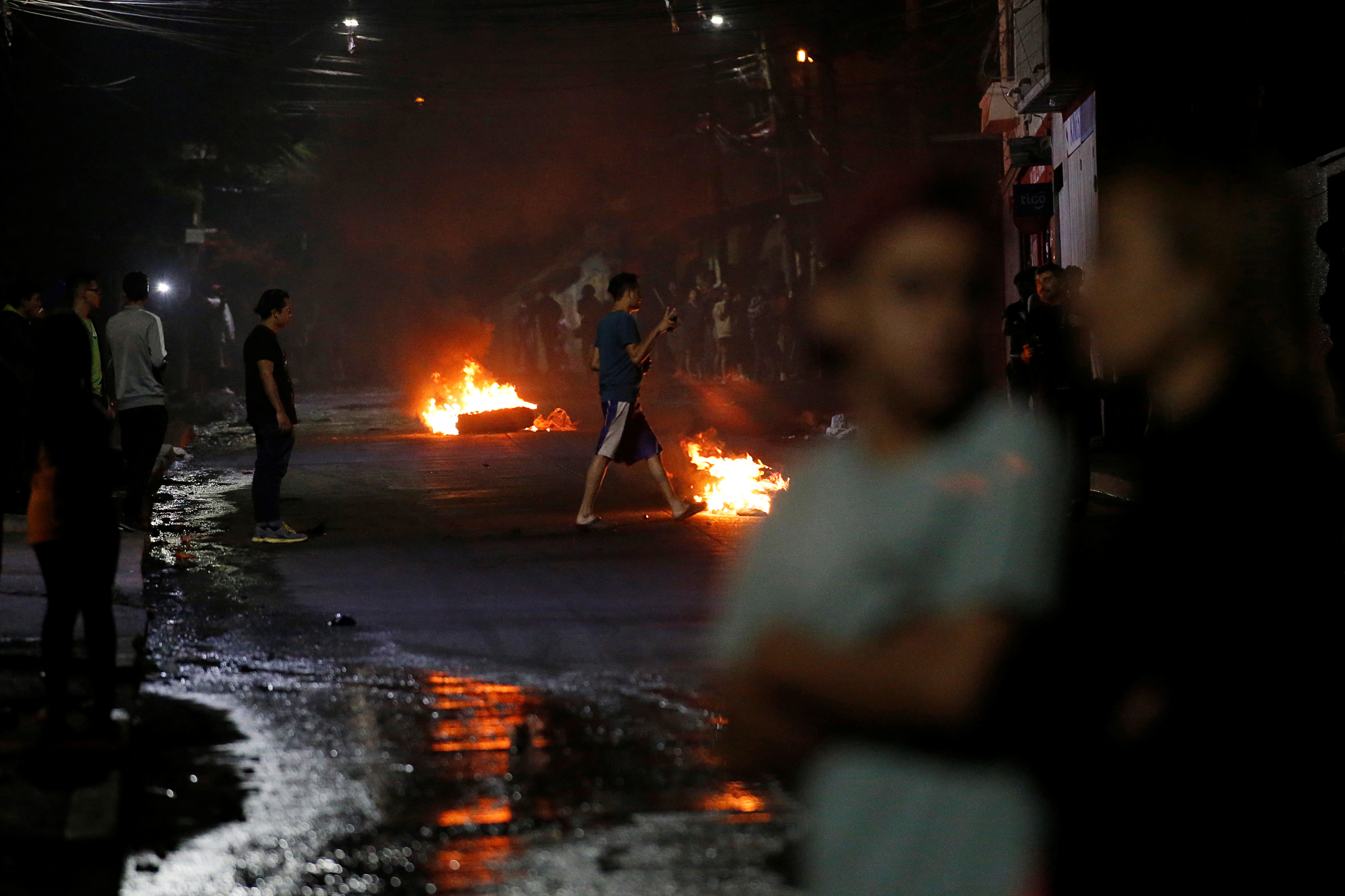 People are seen next to barricades along a street at a protest during curfew while the country is still mired in chaos over a contested presidential election in Tegucigalpa, Honduras, Dec. 3, 2017.