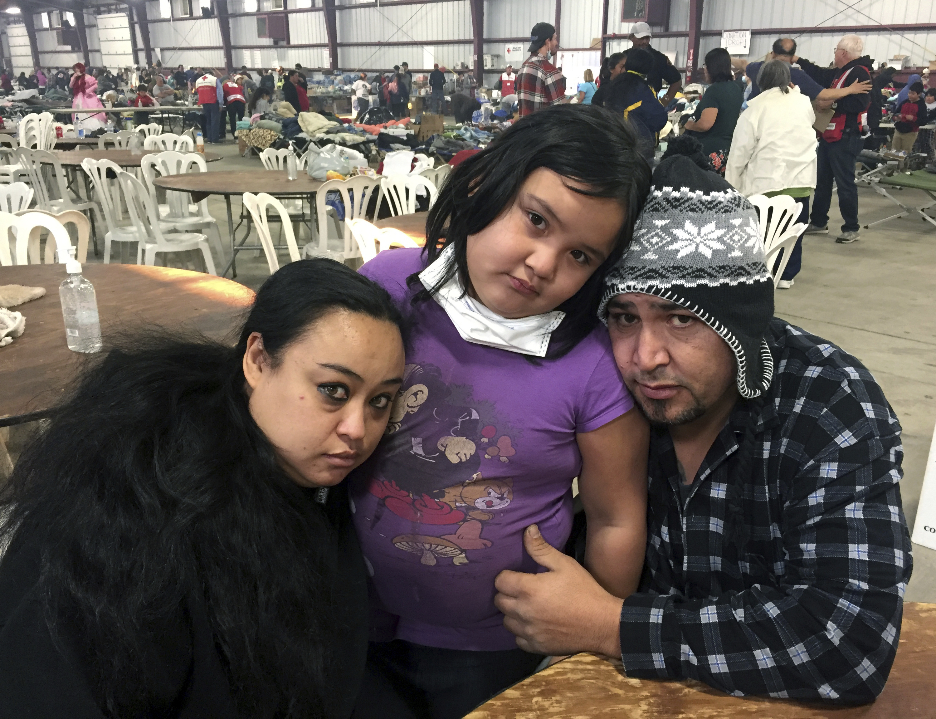 FILE - Wildfire survivors Marolyn Romero-Sim, left, with Hugo Romero-Rodriguez, center, and their 9-year-old daughter, Milagros, sit inside the evacuation center at the Ventura County Fairgrounds in Ventura, Calif., Dec. 6, 2017.