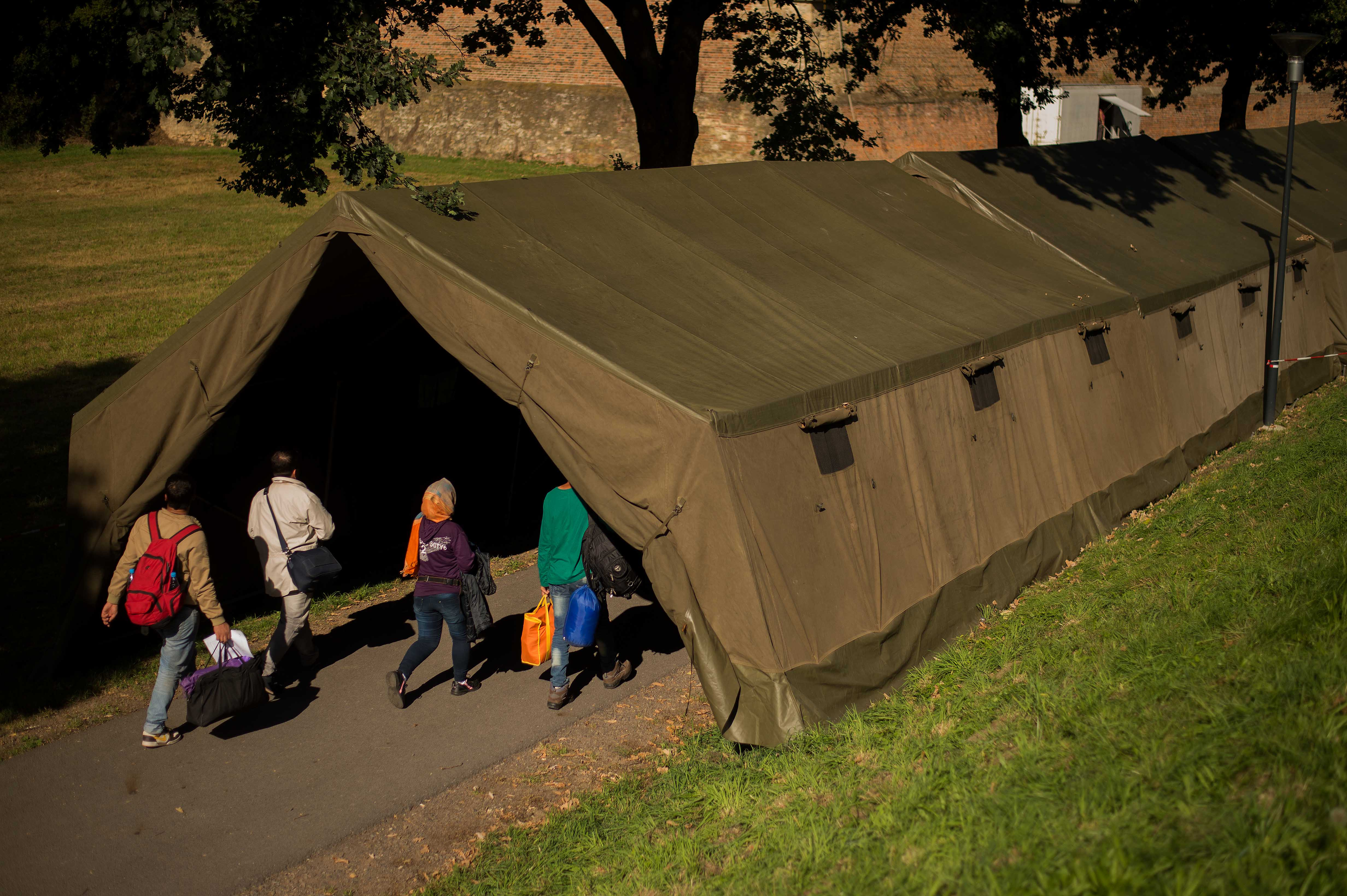 Migrants walk into a makeshift camp after registration  in Bad Radkersburg, Austria, about 210 kms (130 miles) south of Vienna, Austria, Sept. 21, 2015.