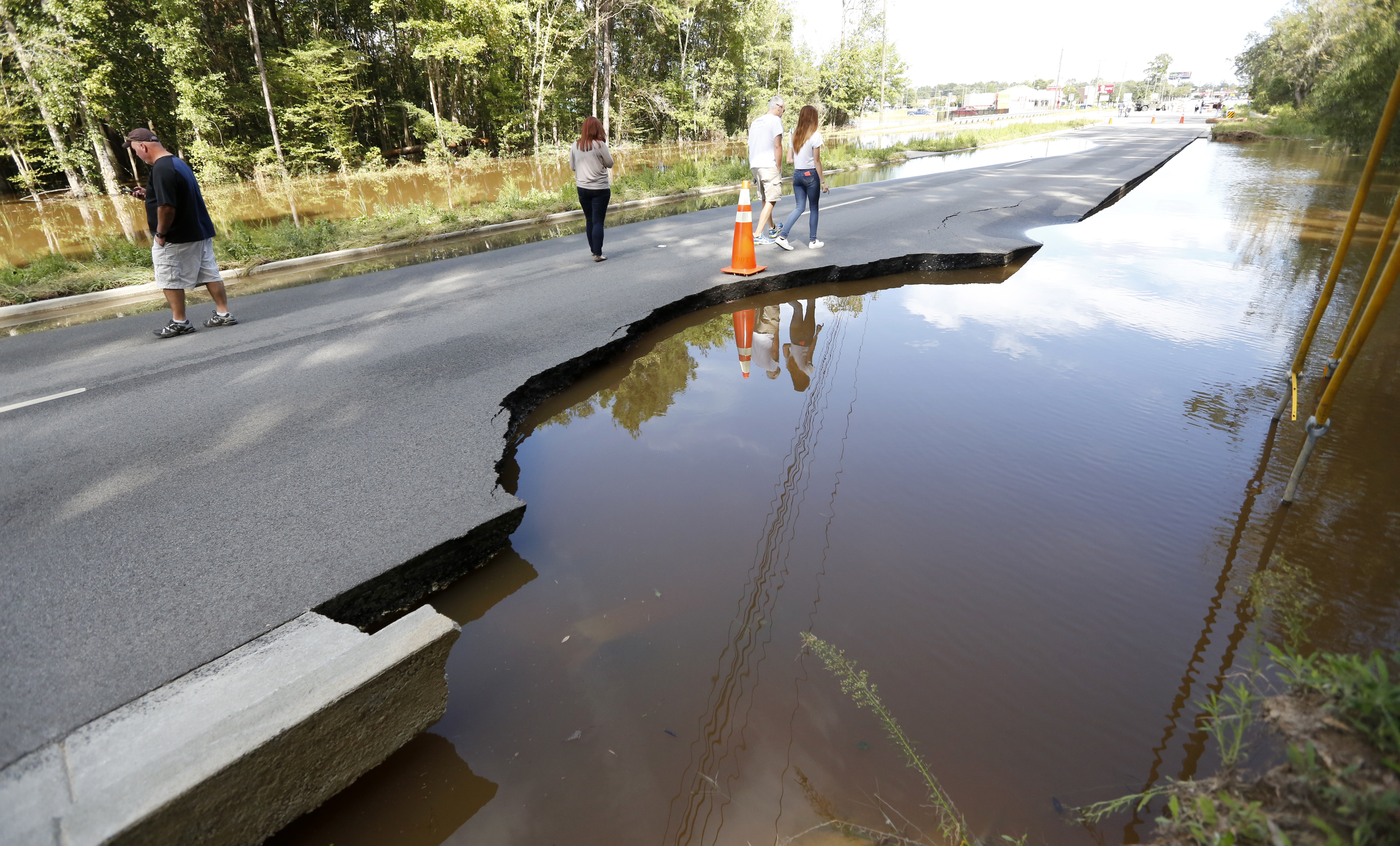 Pedestrians walk down Dorchester Road at Sawmill Branch Canal as it begins to wash away due to floodwaters near Summerville, S.C., Oct. 6, 2015. Residents are concerned that the Ashley river will continue to rise as floodwaters come down from Columbi...