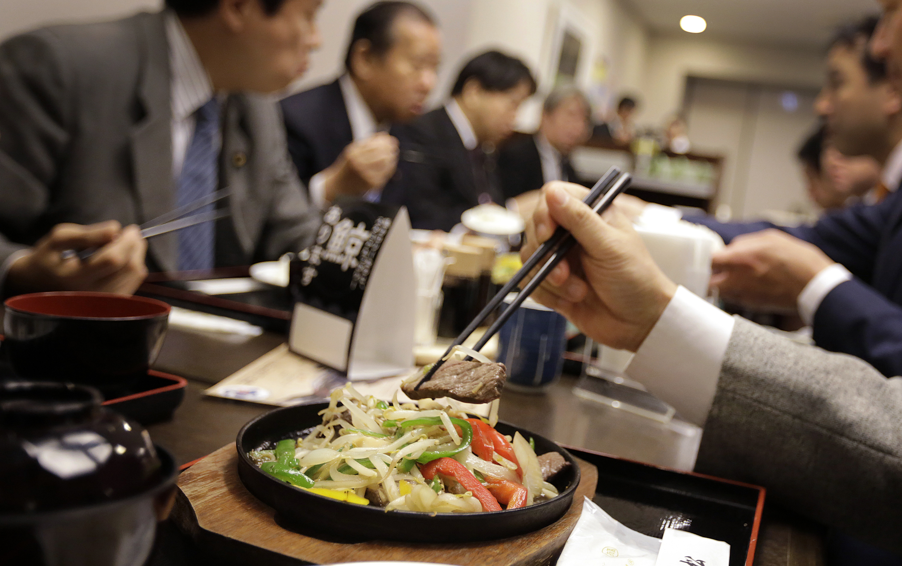 Lawmakers and government officials try whale meat dishes to promote whale meat at a dining room of Ministry of International Trade and Industry in Tokyo Wednesday, Nov. 19, 2014.