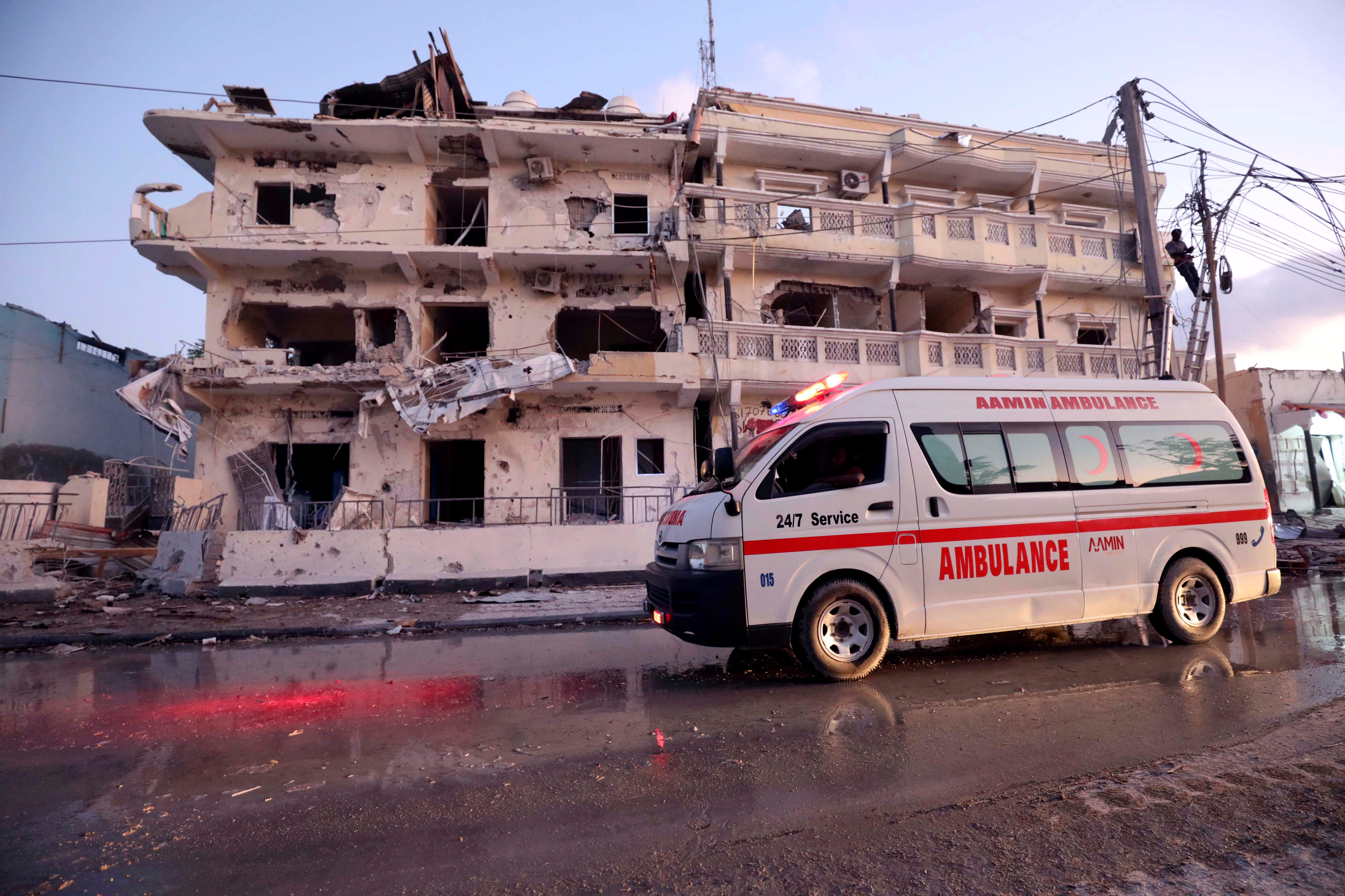 An ambulance passes in front of buildings damaged when a suicide car bomb exploded, targeting a Mogadishu hotel in a business center in Maka al-Mukaram street, Mogadishu, Somalia, March 1, 2019.