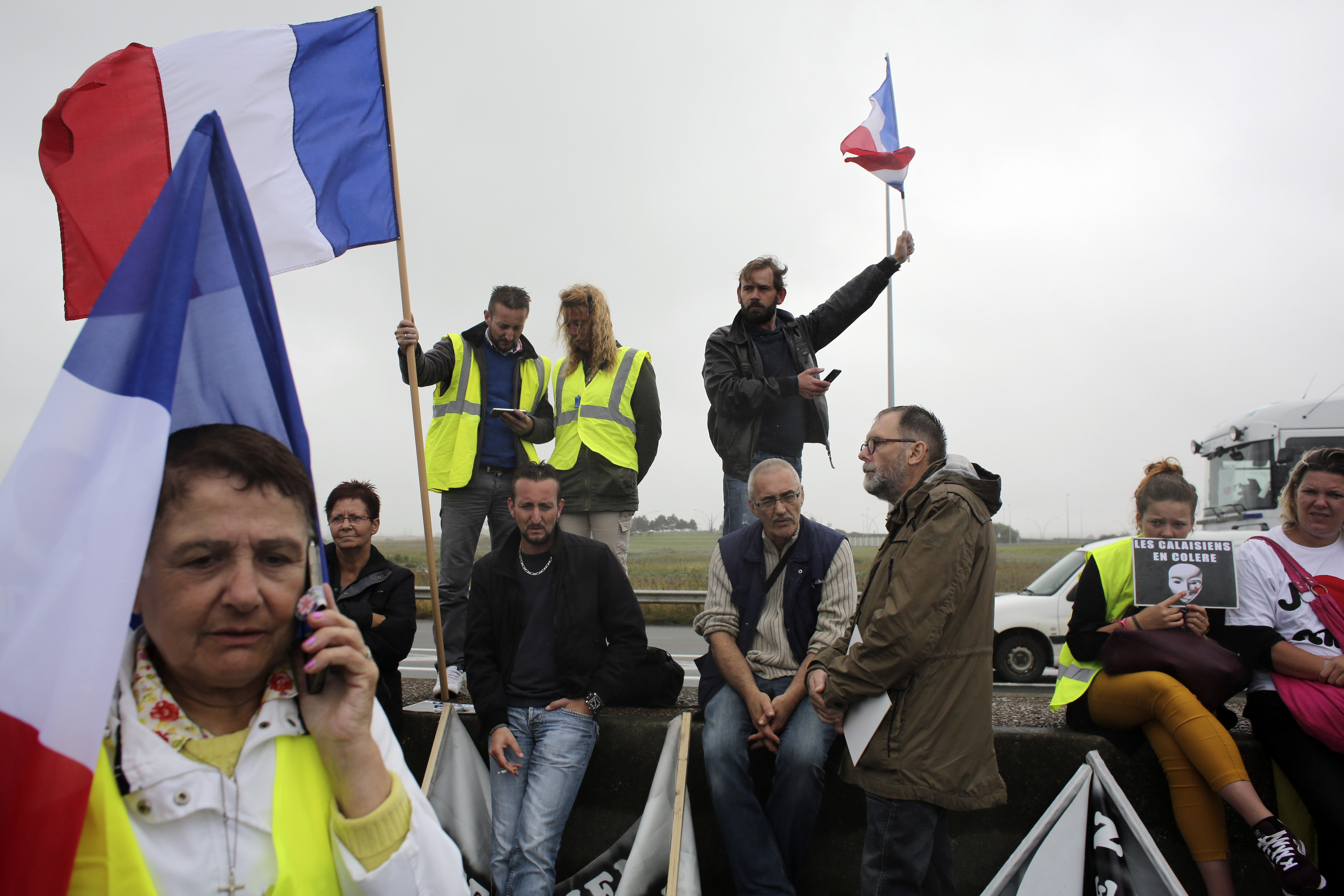 Demonstrators hold French flags as truckers block the highway near Calais, northern France, Sept. 5, 2016.