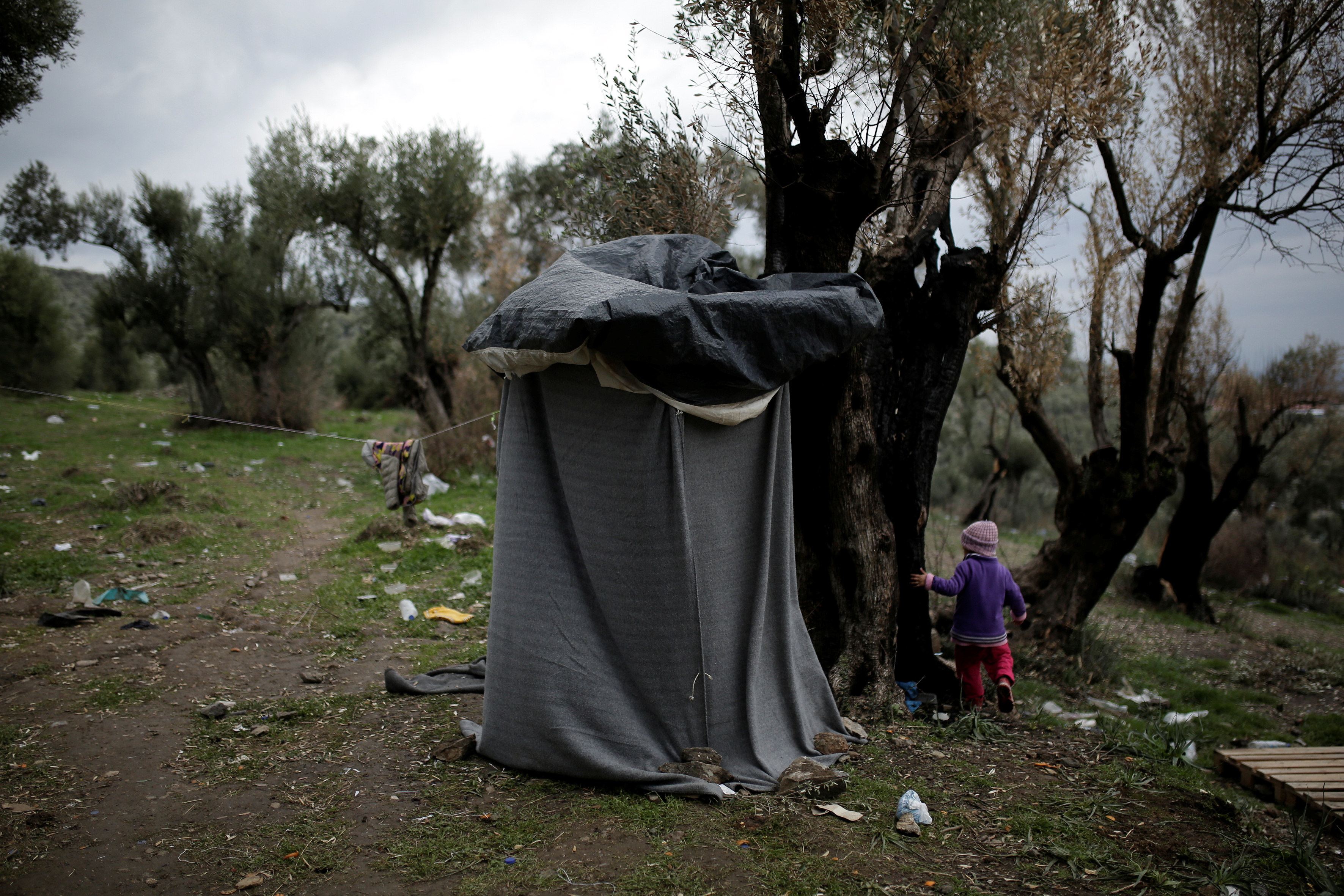 A girl walks next to a self-made shower at a makeshift camp for refugees and migrants next to the Moria camp on the island of Lesbos, Greece, Nov. 30, 2017.