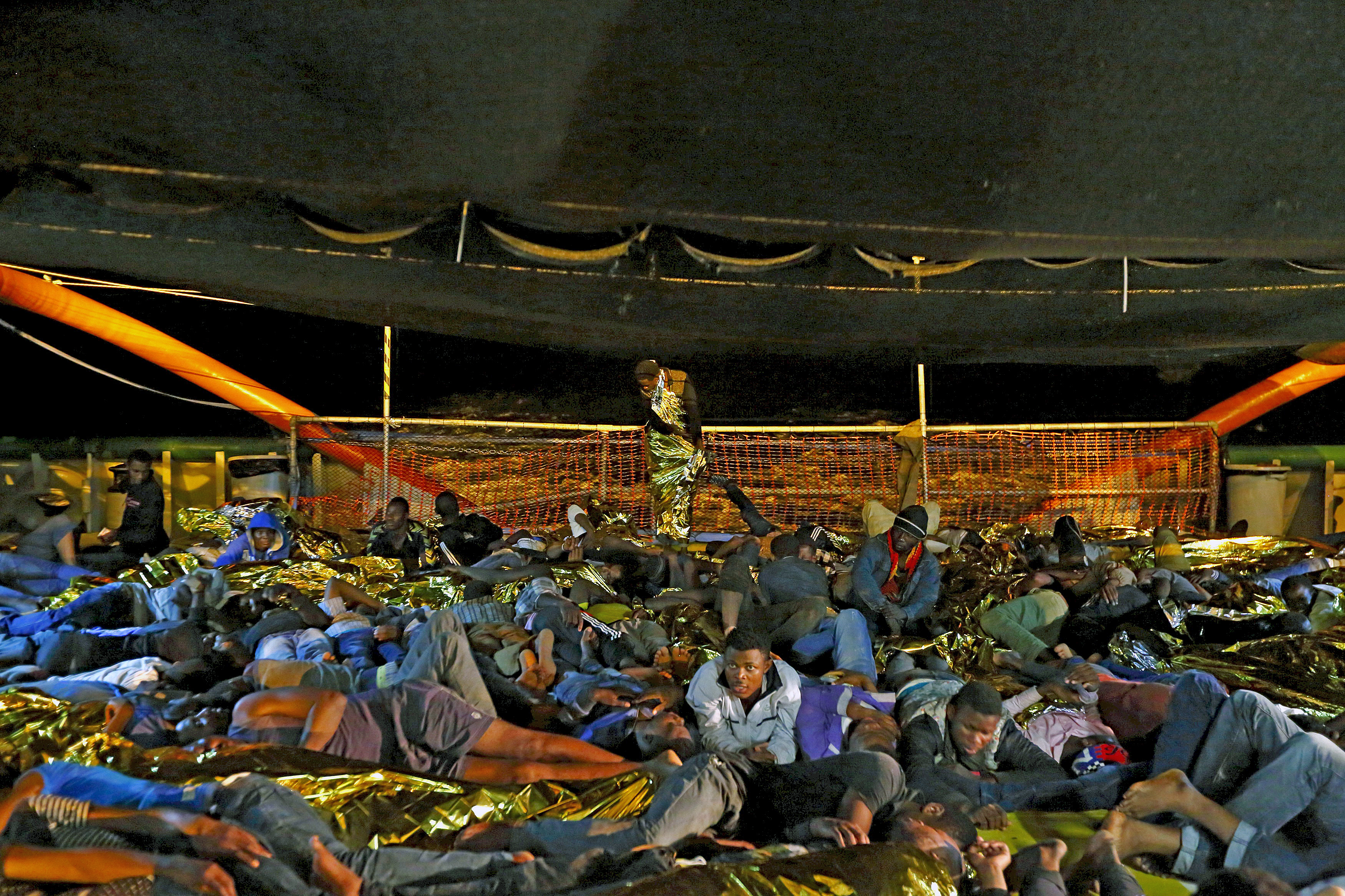 Migrants prepare for a night's sleep on the deck of the Medecins sans Frontieres (MSF) ship Bourbon Argos off the coast of Libya, August 7, 2015.