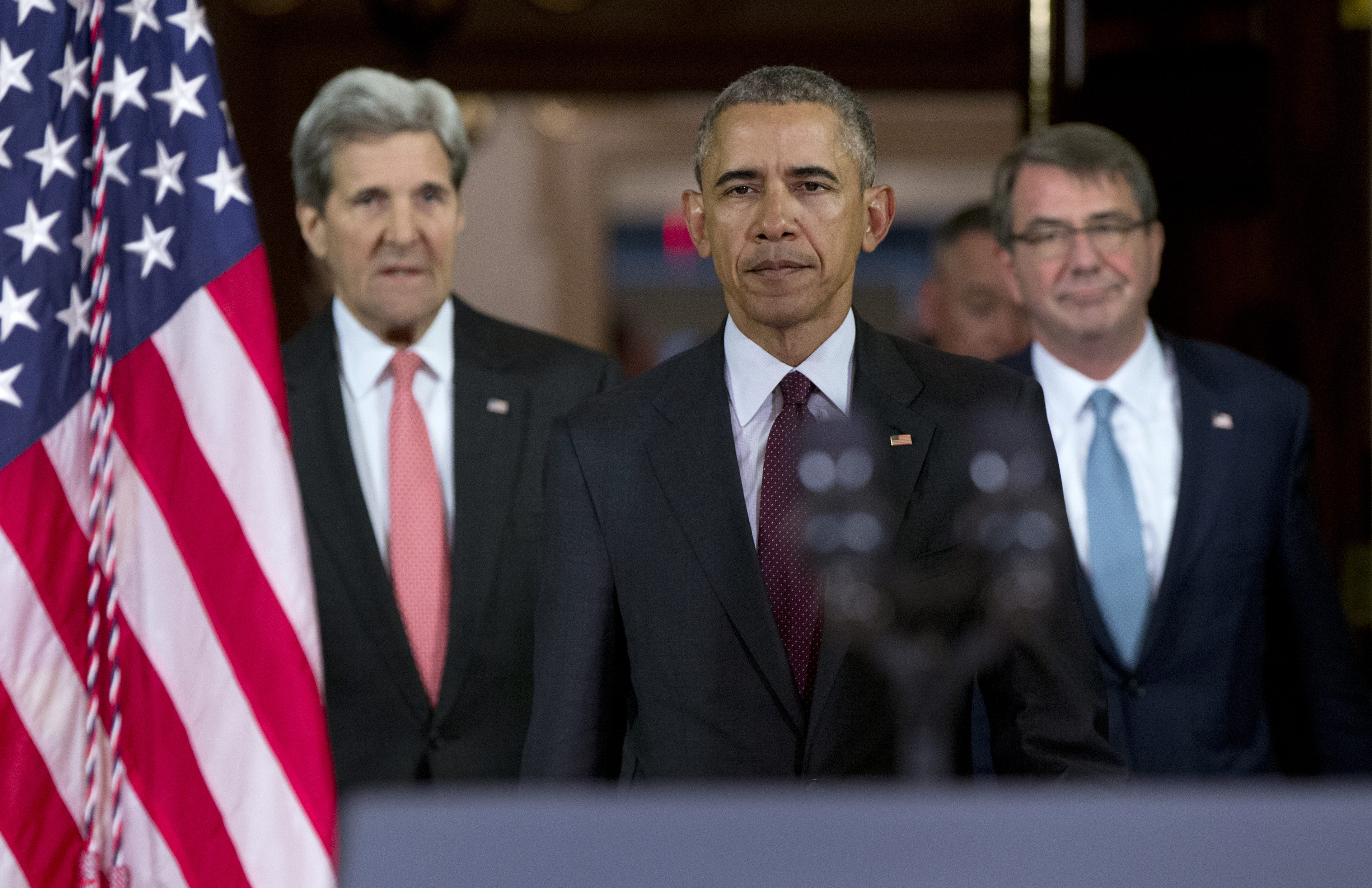 President Barack Obama, center, followed by Secretary of State John Kerry, left, and Defense Secretary Ash Carter right, walks to a podium to speak to media after a meeting of his National Security Council (NSC) at the State Department in Washington,...