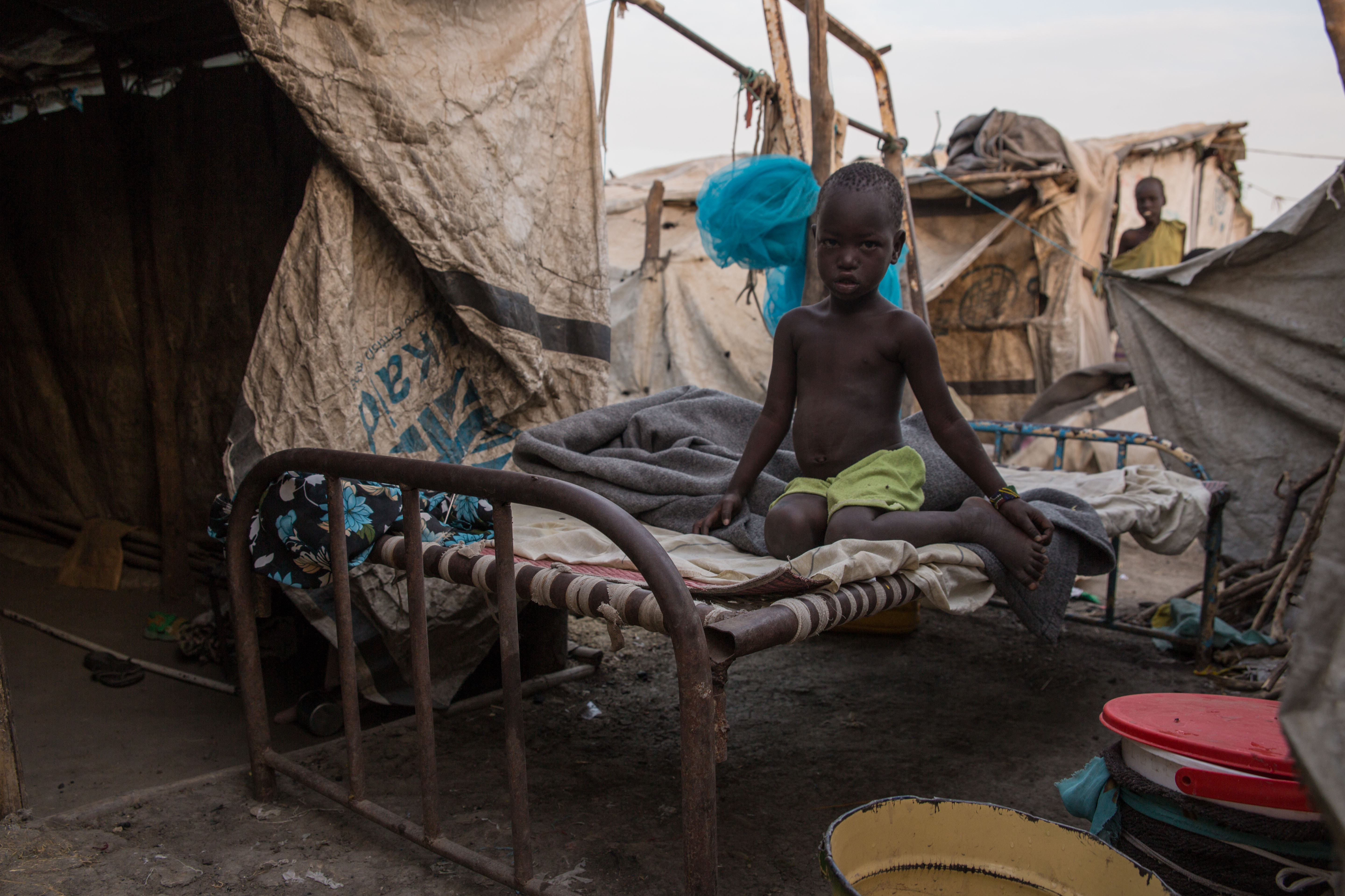 A photo taken on March 13, 2018, shows a child siting on a bed at an internally displaced person camp, hosting more than 24,000 people, in Malakal, South Sudan.
