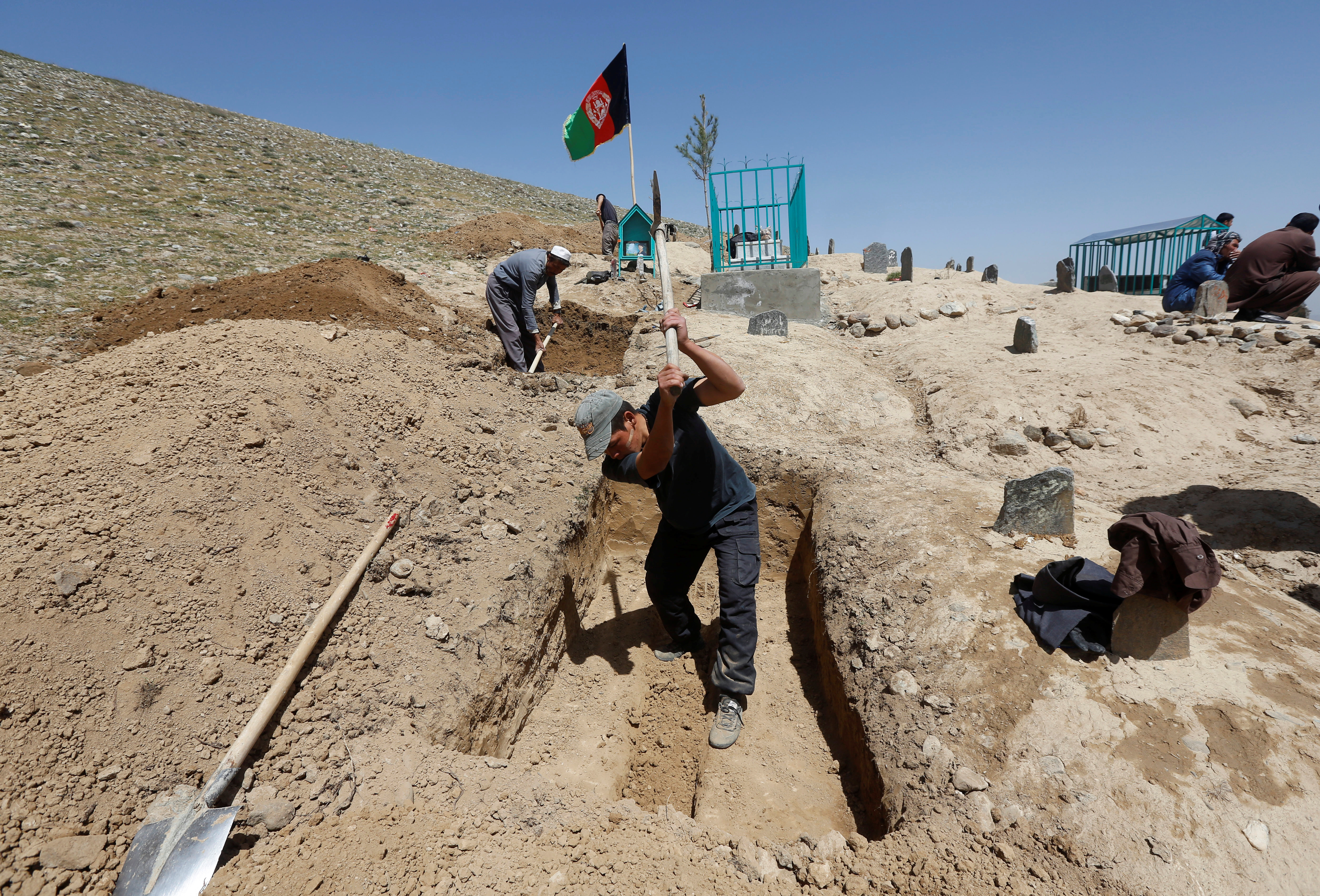 Afghan men dig graves for the victims of Sunday's suicide attack in Kabul, Afghanistan, April 23, 2018.