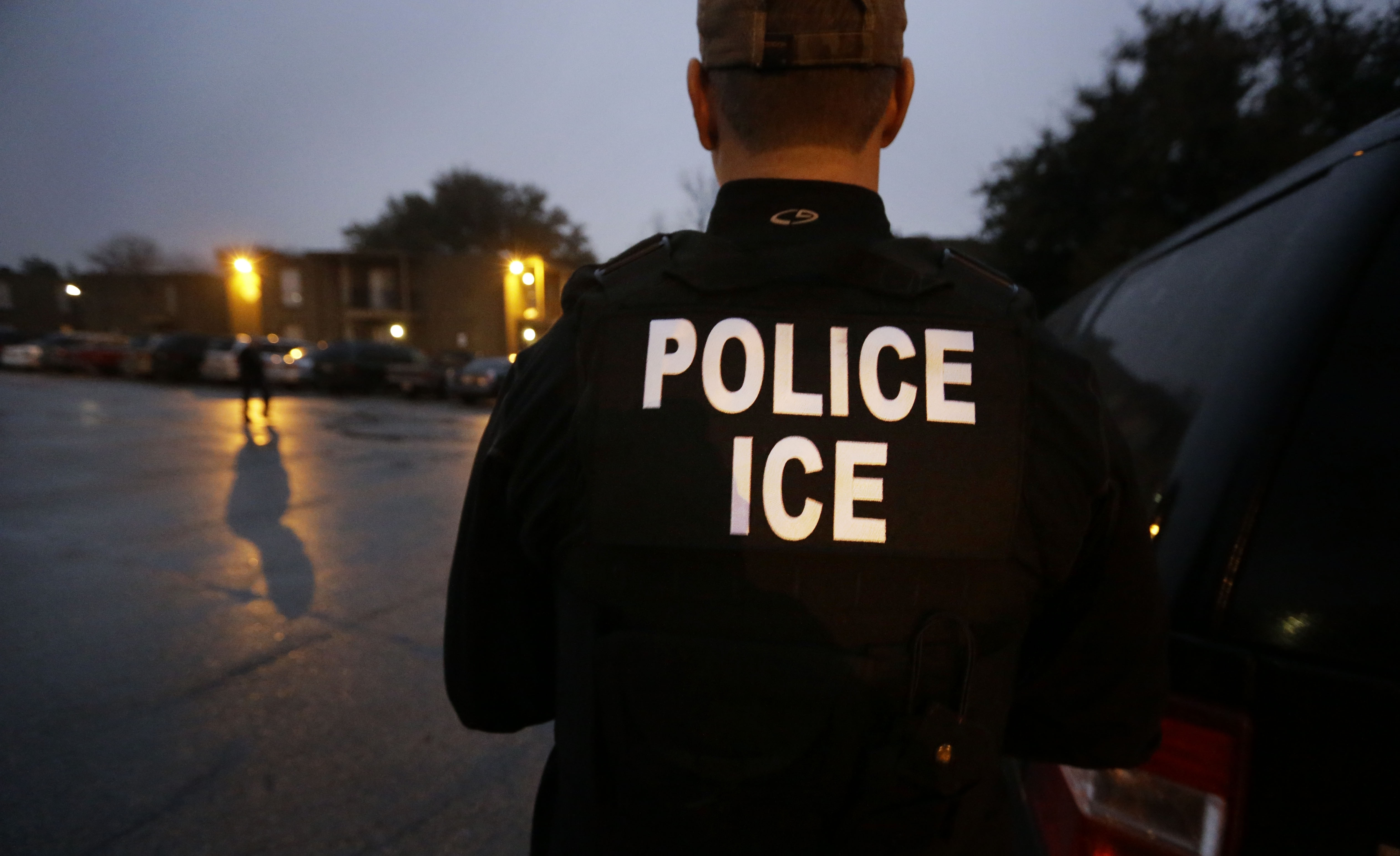 FILE - U.S. Immigration and Customs Enforcement (ICE) agents enter an apartment complex looking for a specific undocumented immigrant convicted of a felony during an early morning operation in Dallas, Texas, March 6, 2015.