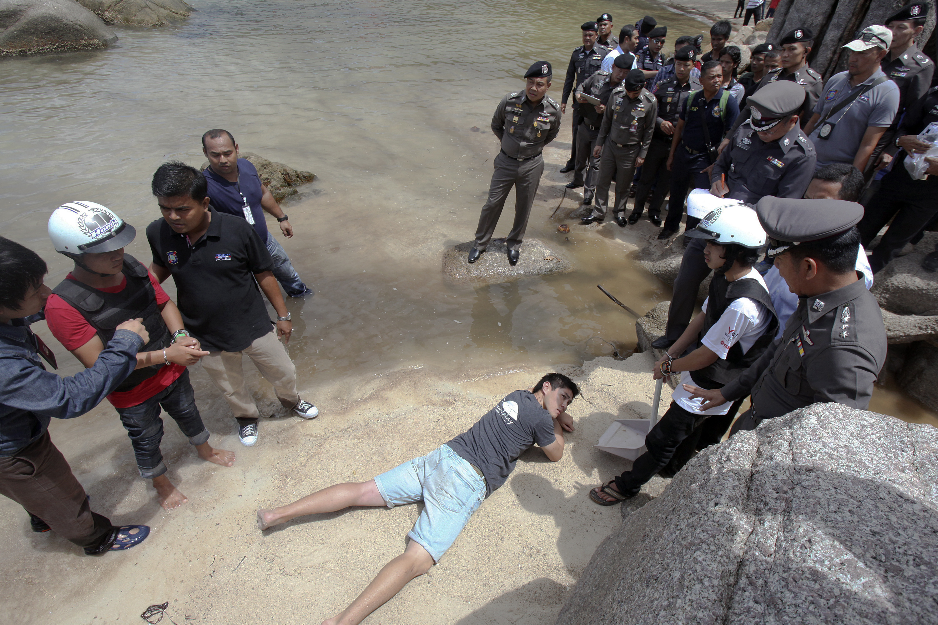 Two workers from Myanmar (wearing helmets and handcuffs), suspected of killing two British tourists on the island of Koh Tao last month, stand near Thai police officers during a re-enactment of the alleged crime, where the bodies of the tourists were...
