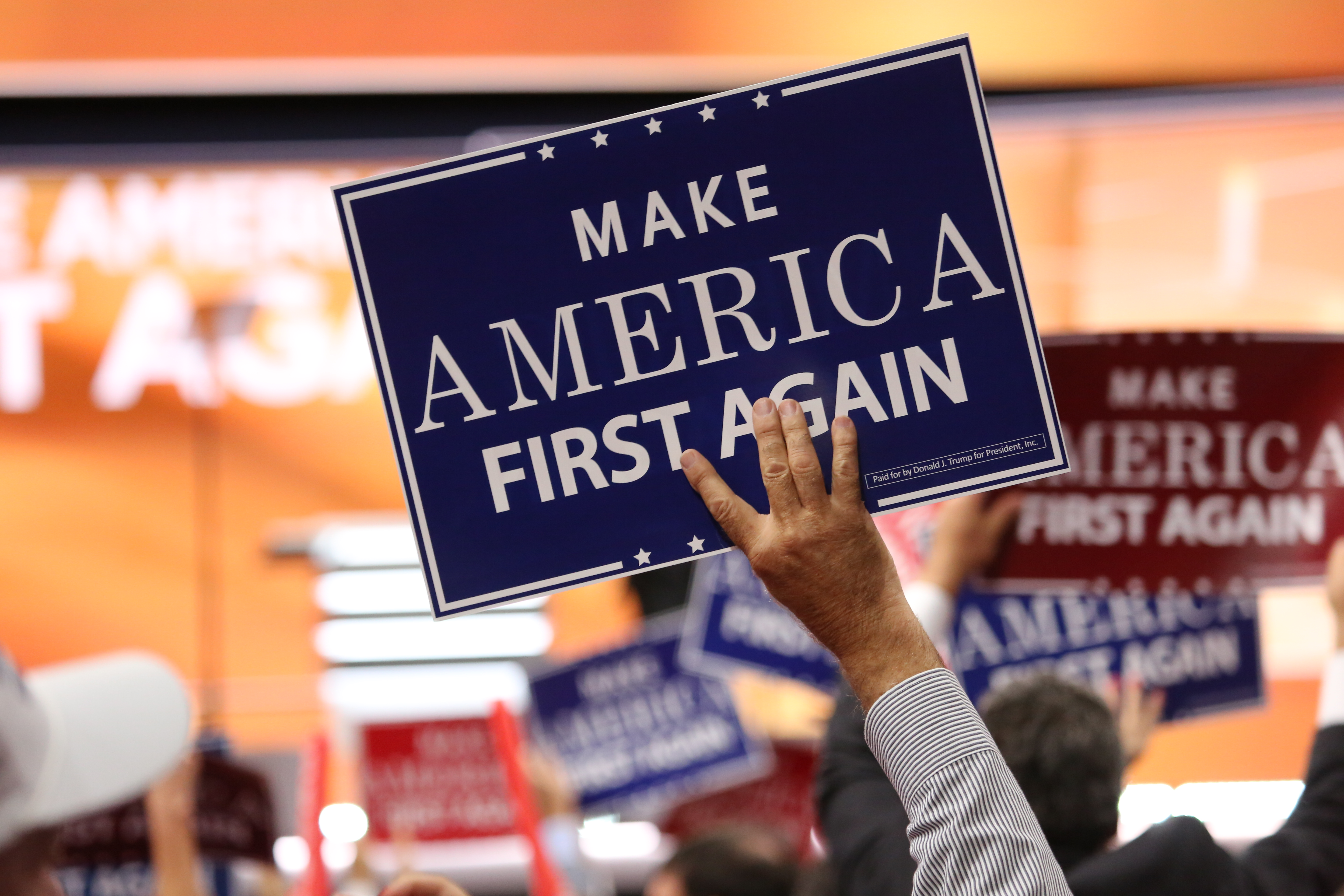 """Delegates hold """"Make America First Again"""" posters on the Republican National Convention floor in Cleveland, Ohio, July 20, 2016. (Photo: Ali Shaker / VOA)"""