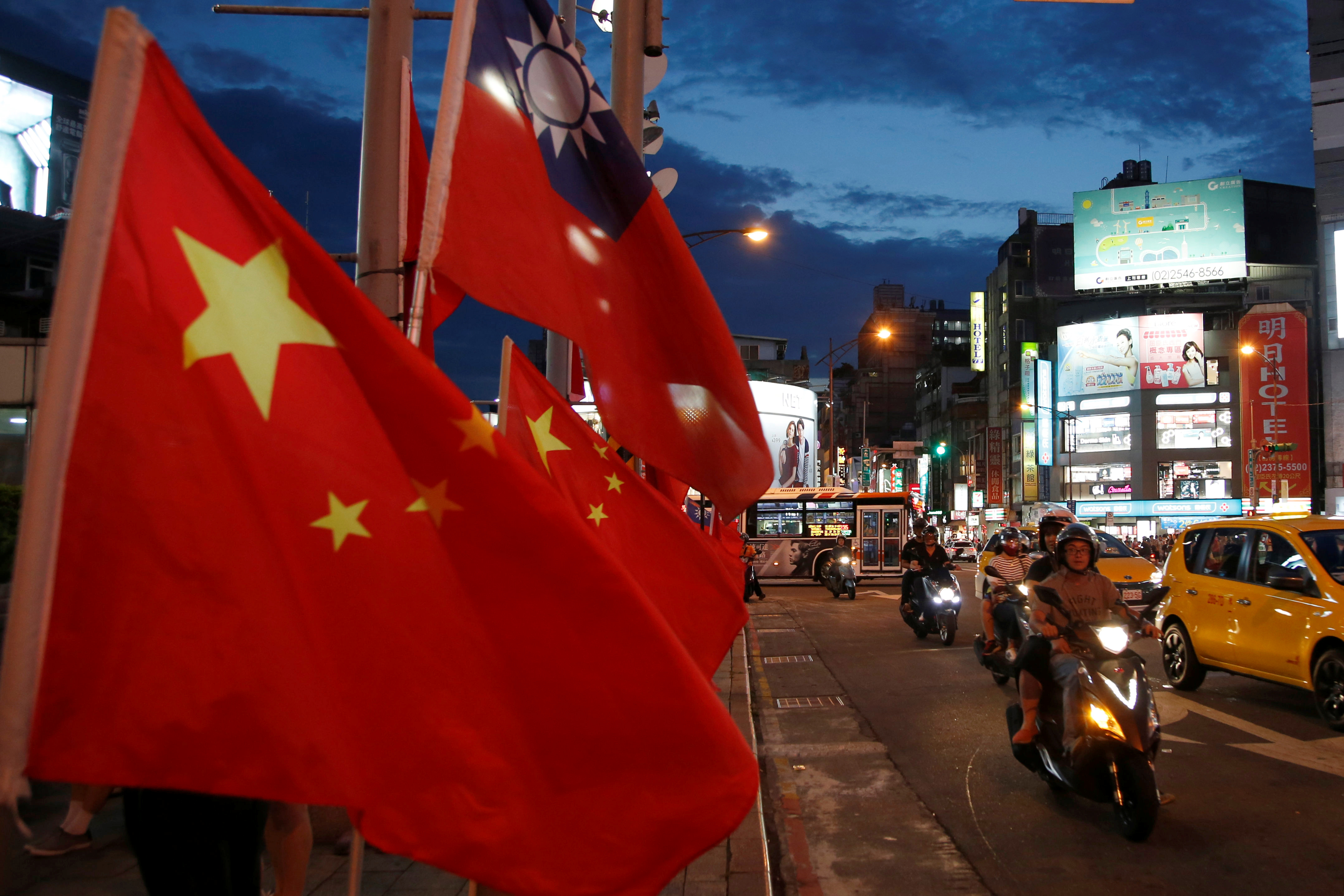 FILE - Flags of China and Taiwan flutter next to each other during a rally calling for peaceful reunification, days before the inauguration ceremony of President Tsai Ing-wen, in Taipei, Taiwan, May 14, 2016.