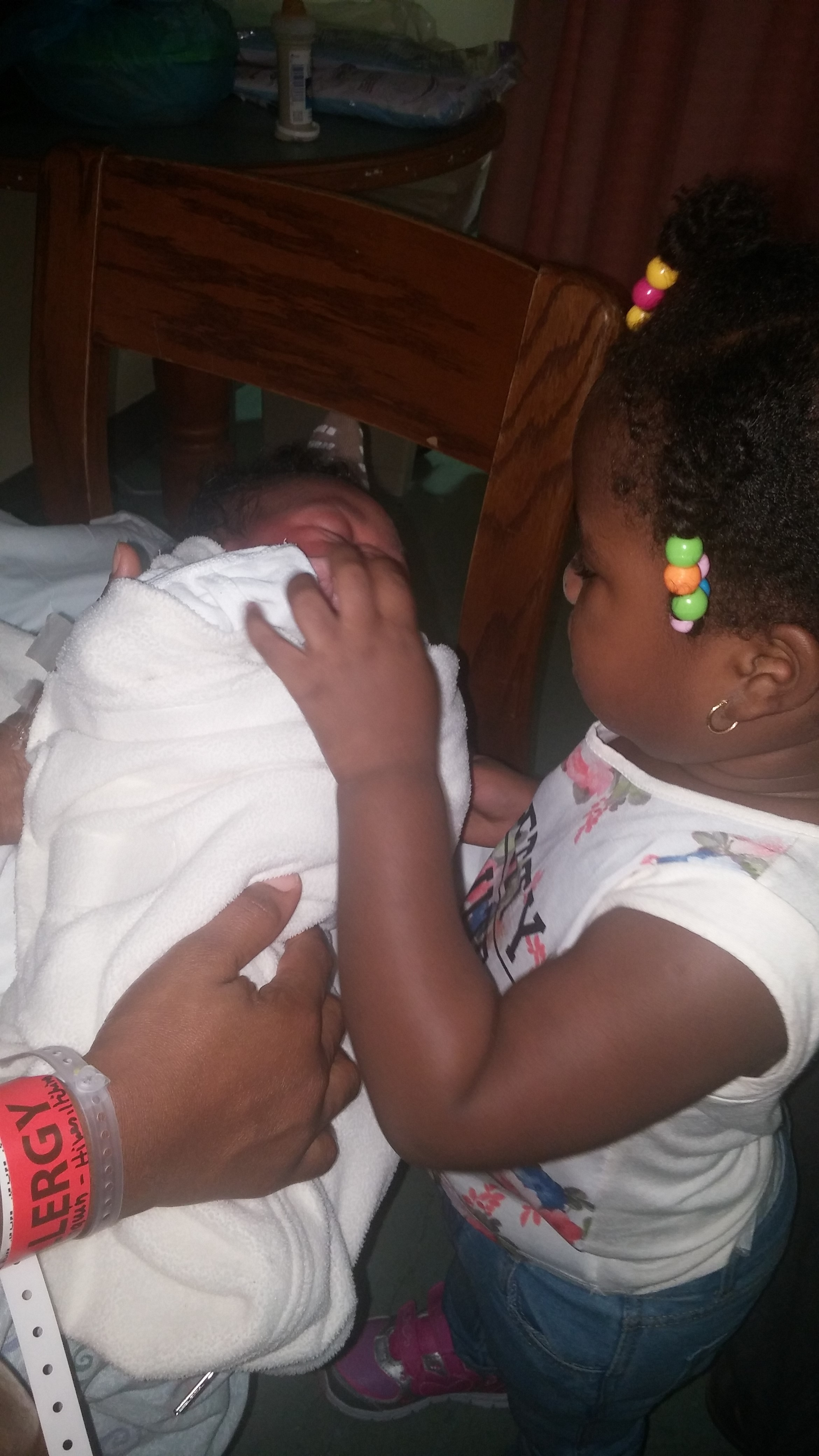 Agnes' daughter holds her baby brother, born in a Washington, D.C. hospital, for the first time. (J.Oni/VOA)