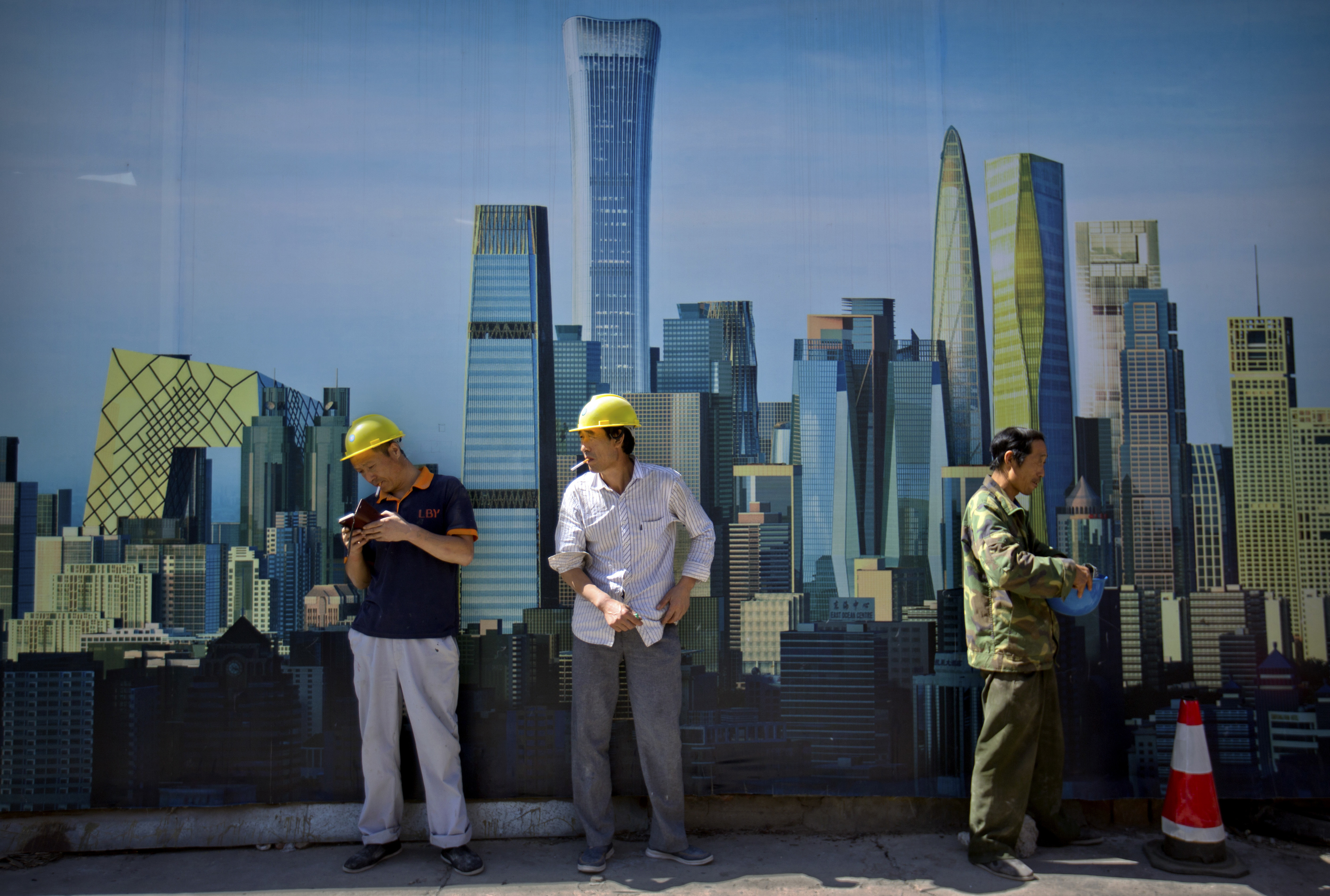 FILE - Workers smoke outside of a construction site in the central business district in Beijing, Sept. 22, 2017.