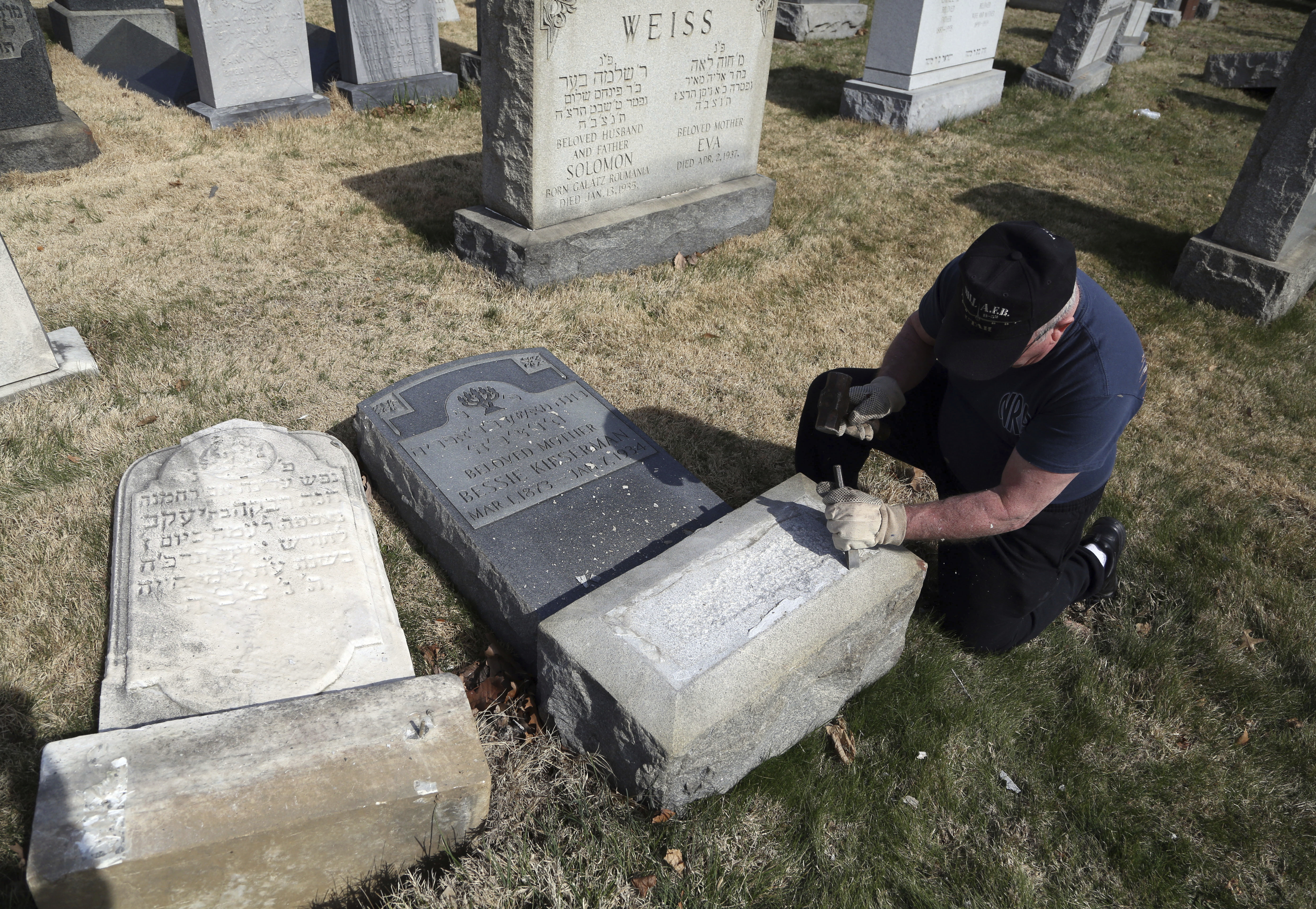 Trump supporter Bob, who declined to give his last name, volunteers his time and prepares the base of a damaged headstone, Feb. 28, 2017, in Philadelphia. Scores of volunteers are expected to help in an organized effort to clean up and restore the J