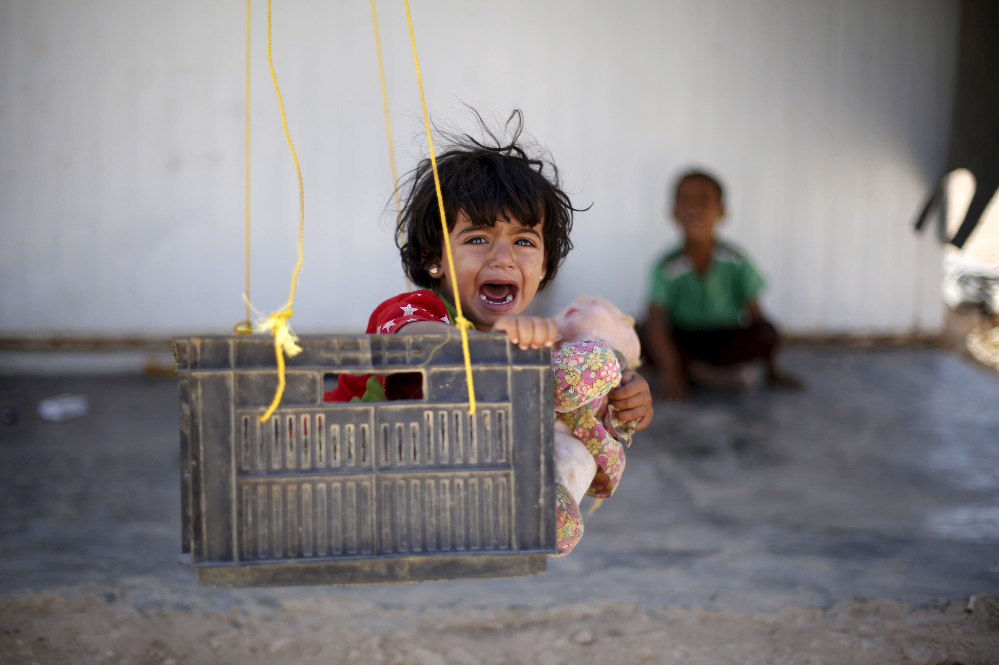 A Syrian refugee child reacts while sitting in a swing in Al Zaatari refugee camp, in the Jordanian city of Mafraq, near the border with Syria, September 19, 2015.