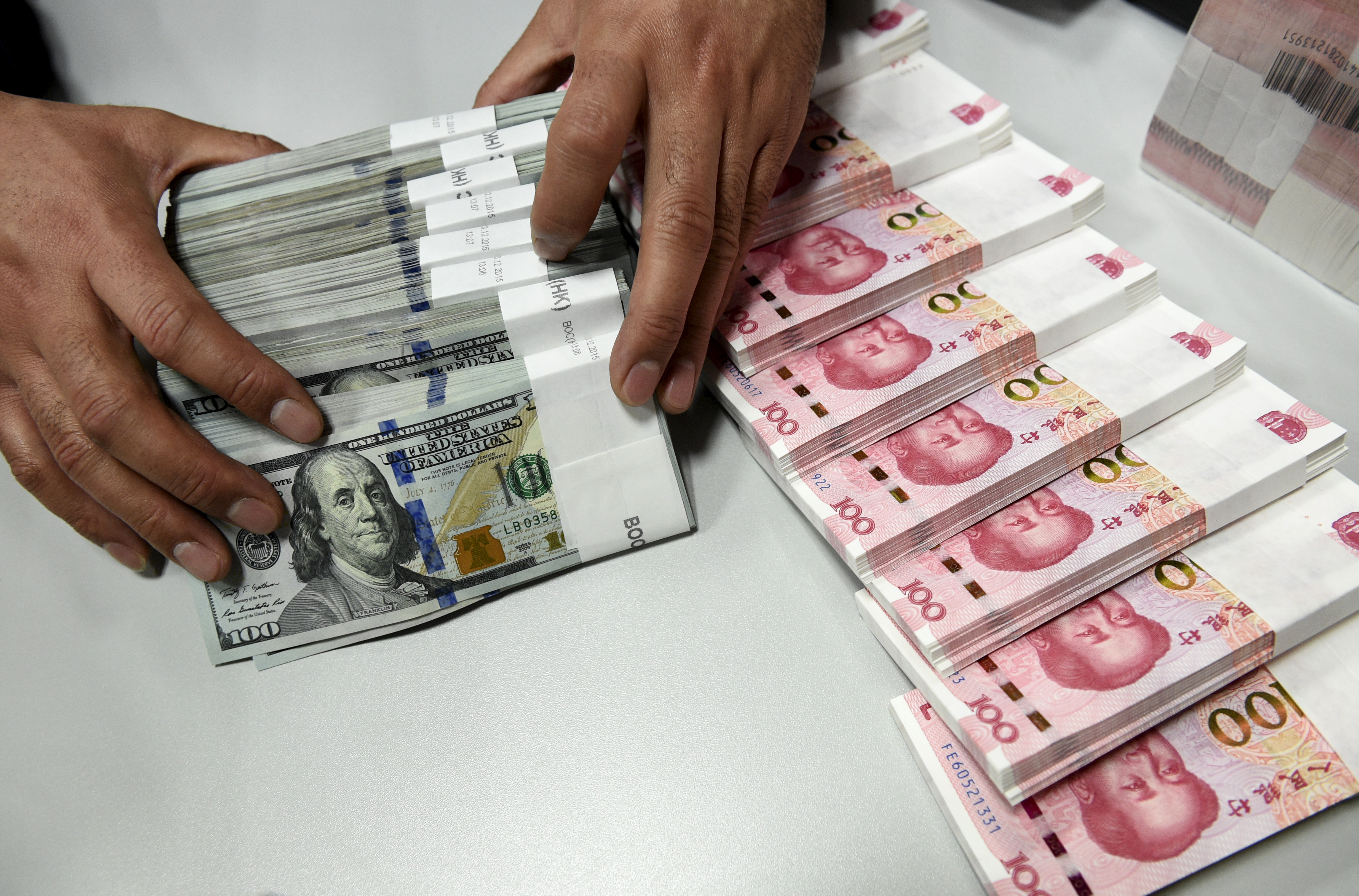 A clerk counts Chinese yuan and U.S. dollar banknotes at a branch of Bank of China in Taiyuan, China, Jan. 4, 2016. China's currency has been slipping in value since Donald Trump became president-elect.