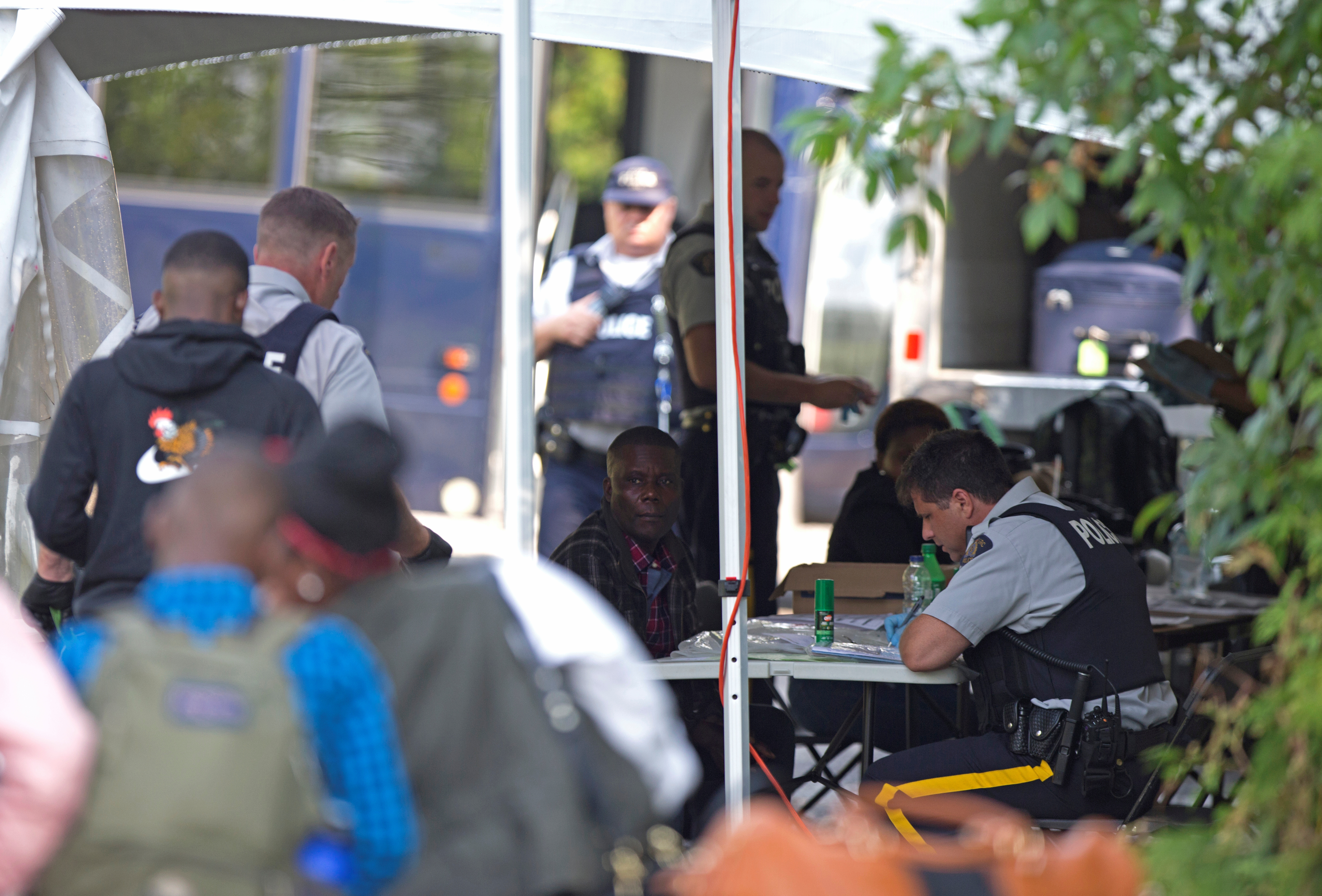 Refugees are processed by the Royal Canadian Mounted Police (RCMP) after crossing illegally into Canada at the U.S.-Canada border on Roxham Road from Champlain, New York, August 3, 2017.