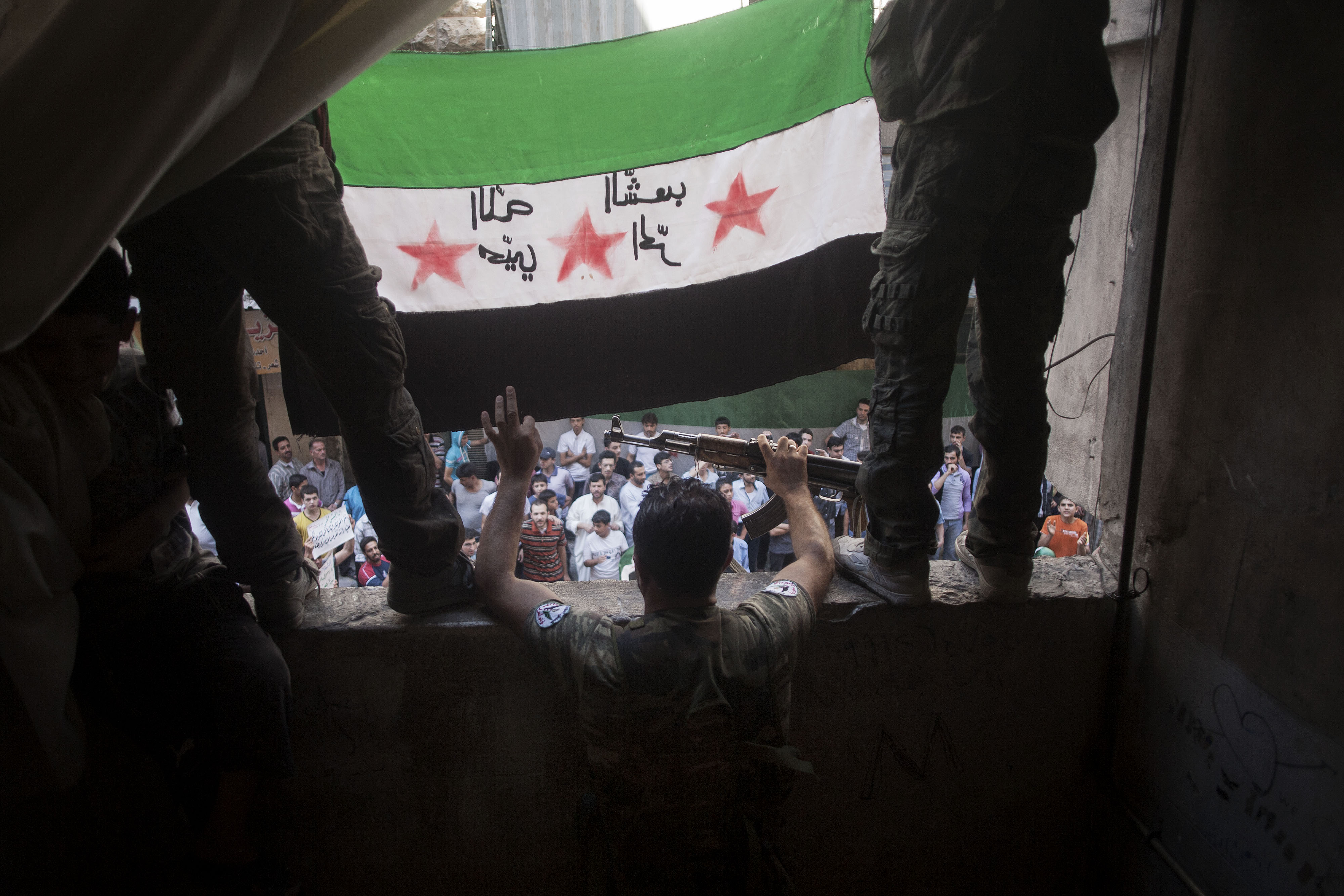 FILE -  Free Syrian Army rebels hold a revolutionary flag during a demonstration in the Bustan al-Qasr neighborhood of Aleppo, Syria.