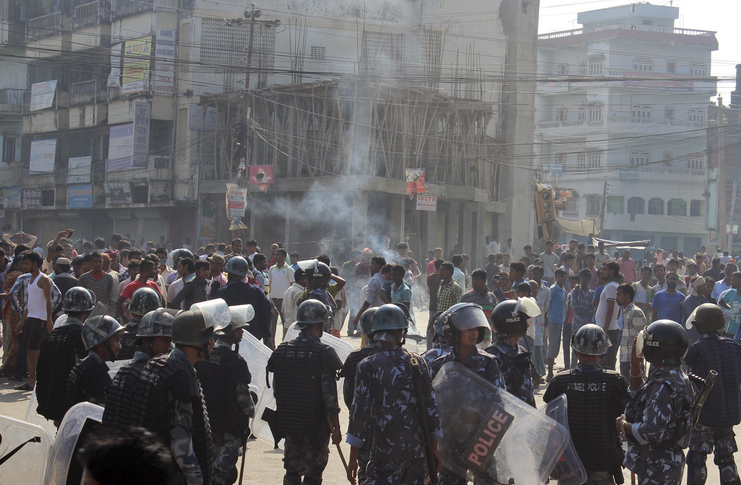 Ethnic Madhesi protesters stand near smoke from a tire set on fire by them, as Nepalese policemen stand guard near the Central Development Office at Birgunj, a town on the border with India, Nepal, Nov. 2, 2015.