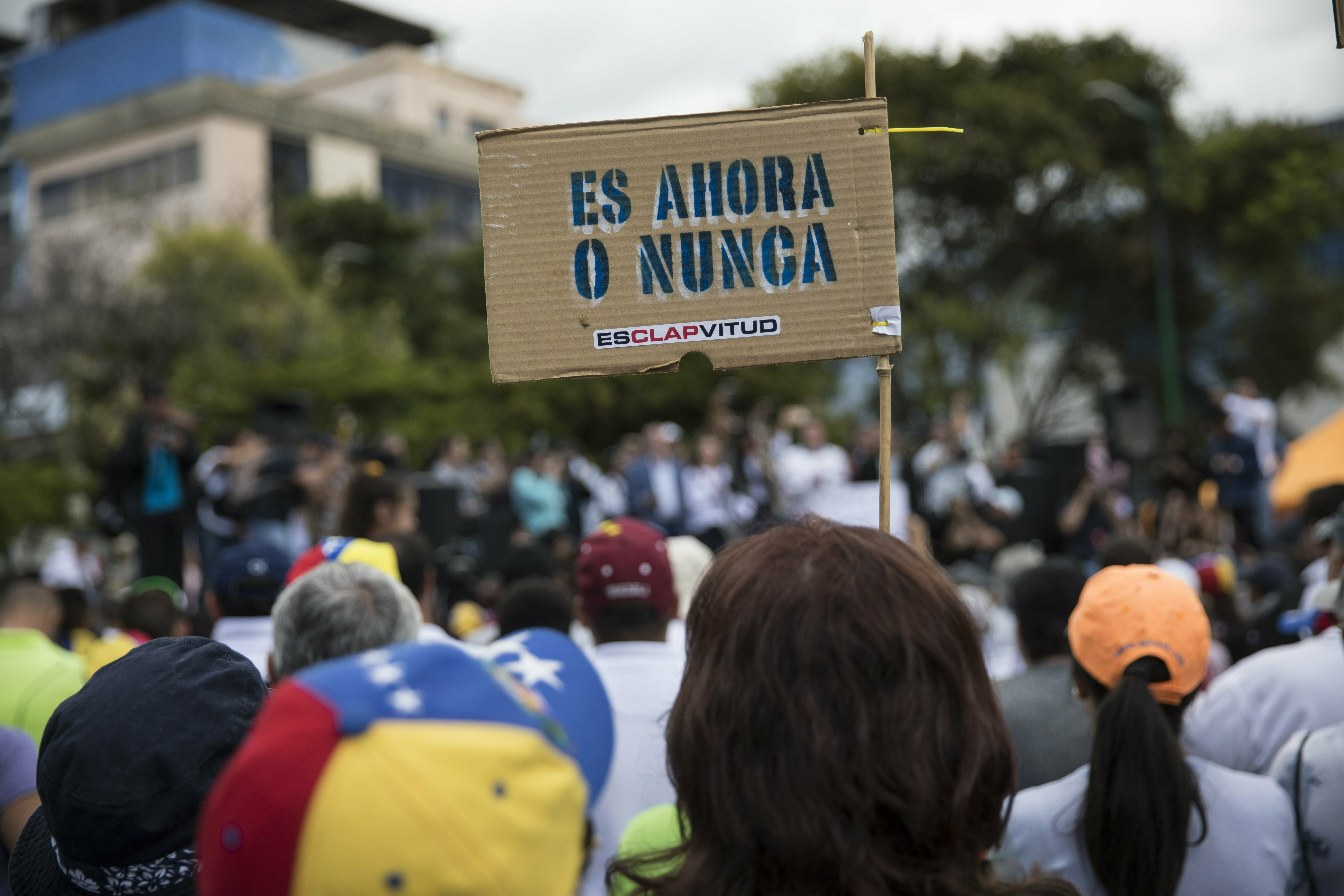 """A member of the opposition holds a sign with message that reads in Spanish:""""It's now or never"""", during a rally to propose amnesty laws for police and military, in Las Mercedes neighborhood of Caracas, Venezuela, Jan. 29, 2019."""