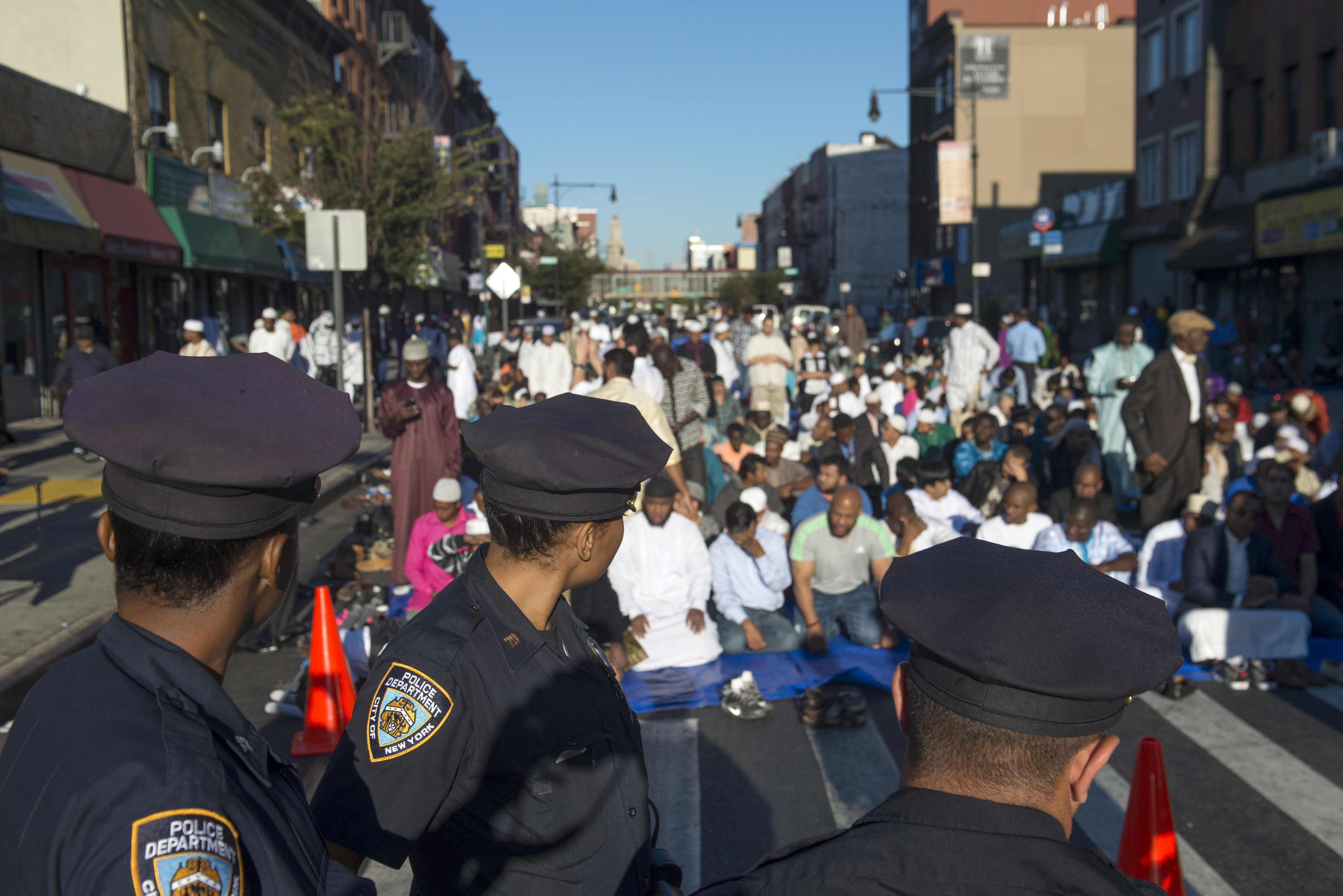 FILE - New York Police Department (NYPD) officers stand near worshippers as they gather outside the Masjid At-Taqwa mosque ahead of Eid Al-Adha prayers in the Brooklyn borough of New York, Sept. 24, 2015.