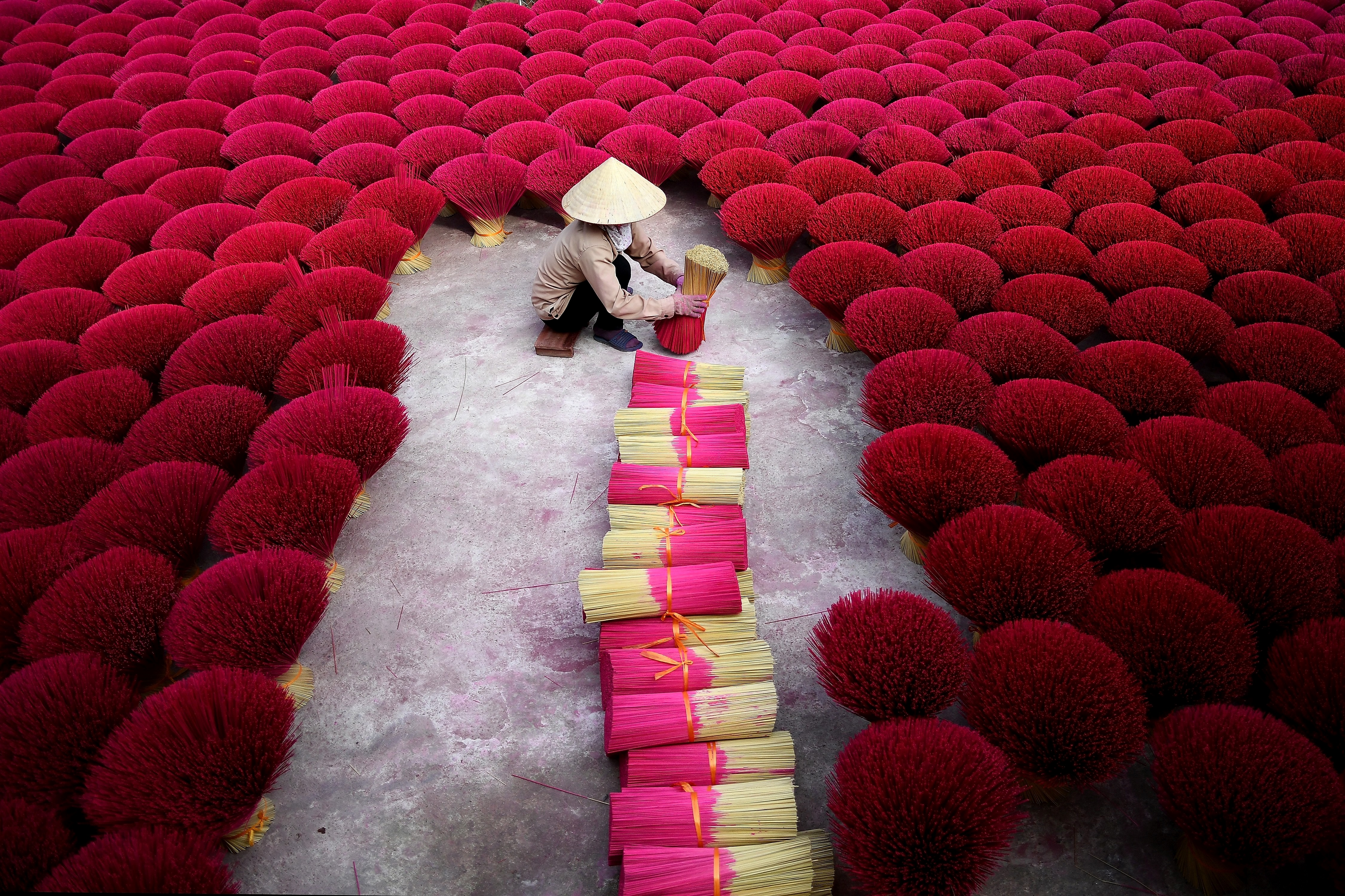 This picture taken on January 3, 2019 shows a Vietnamese woman collecting incense sticks in a courtyard in the village of Quang Phu Cau on the outskirts of Hanoi.