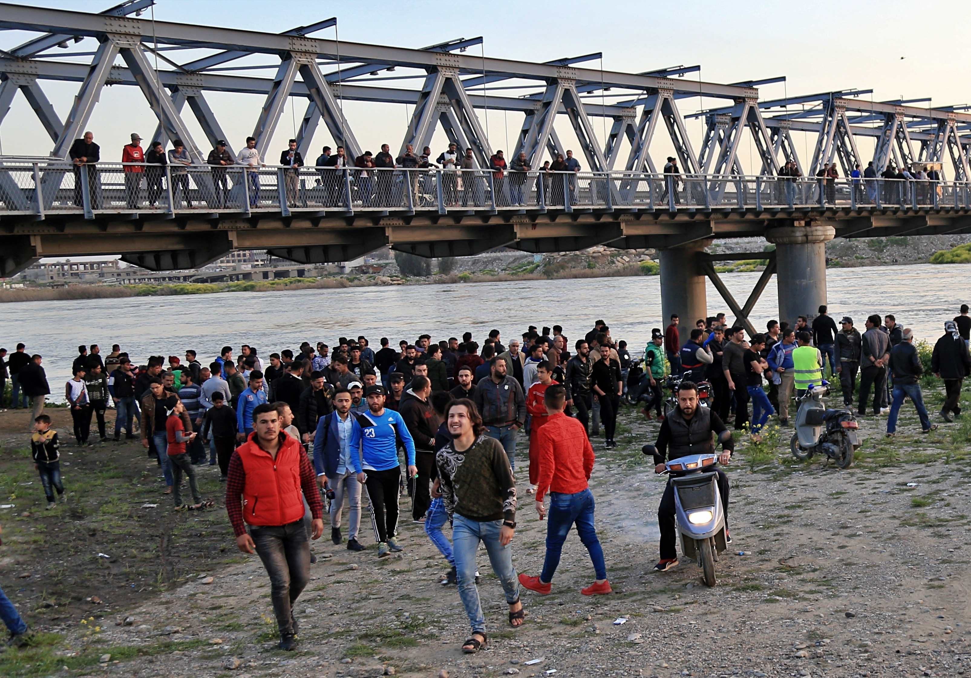 People and relatives of victims waiting on the bank of the Tigris river where the ferry sank in Mosul, Iraq, Thursday, March 21, 2019.