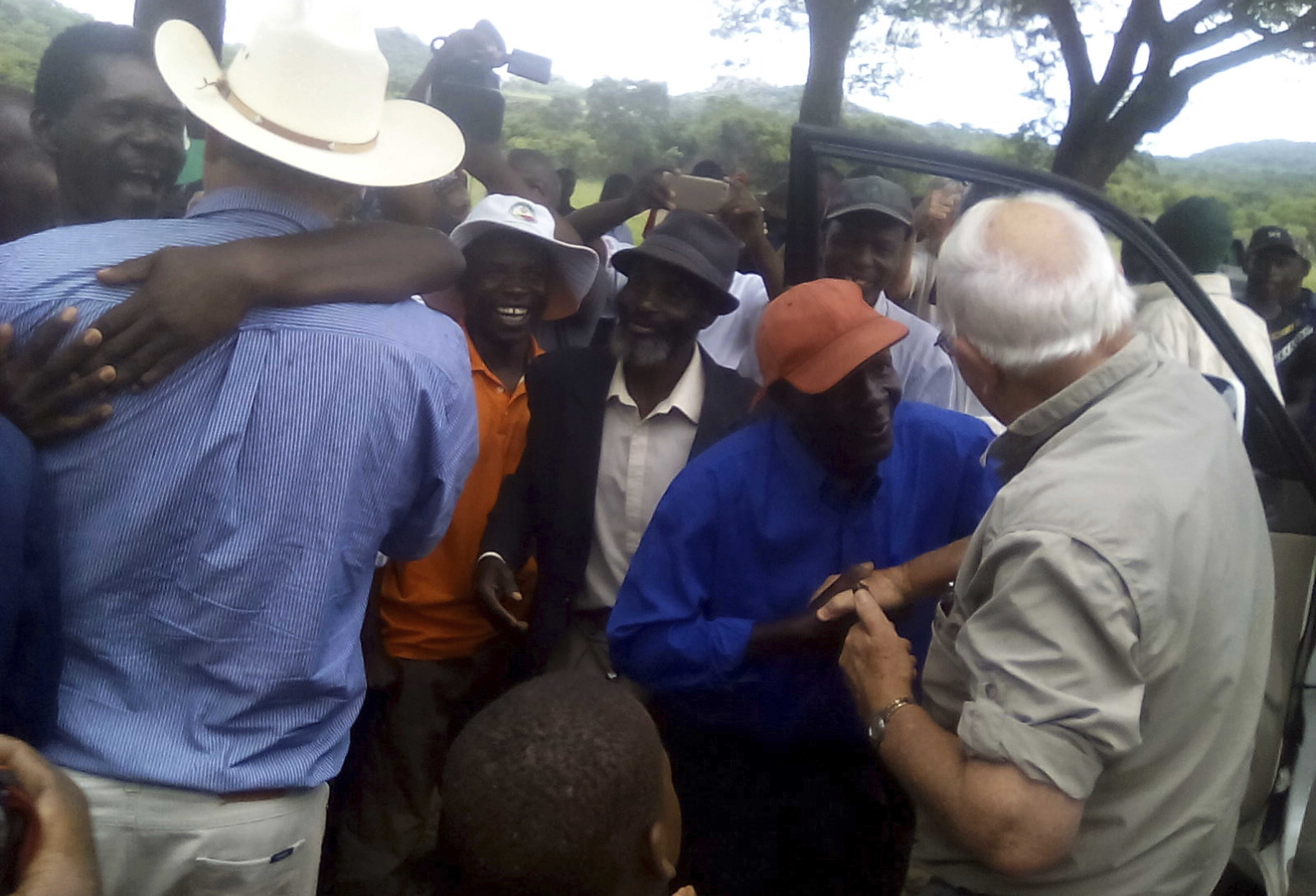 Farmers Robert Smart, right, and his son, Darryn, are welcomed back to their farm, Lesbury, by workers and community members, Dec. 21, 2017 in Tandi, Zimbabwe.